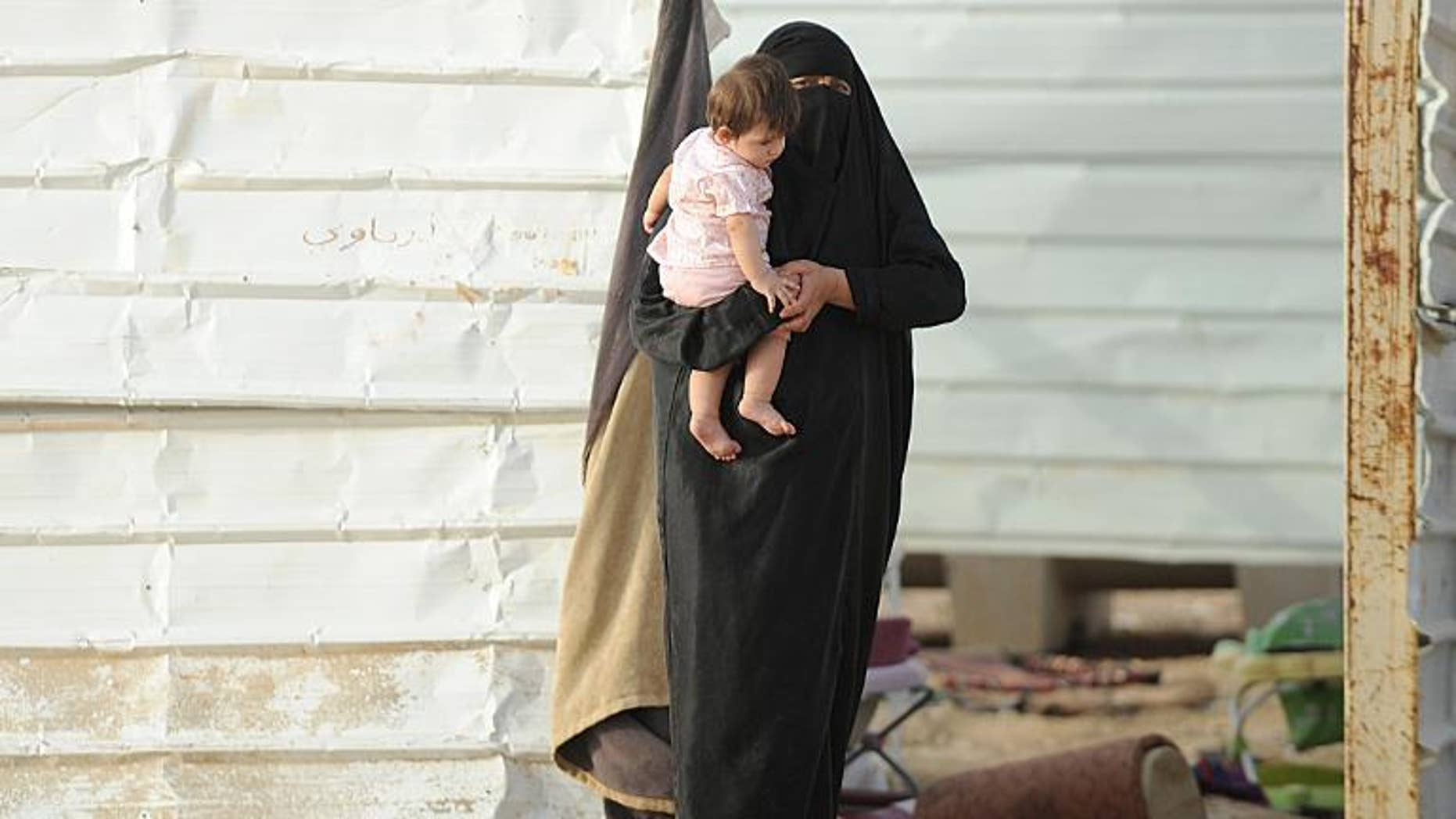A stateless woman carries her child at her makeshift shelter in an impoverished neighborhood of Riyadh on July 10, 2013