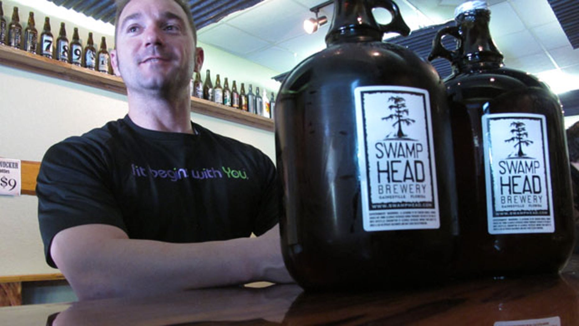 Mar. 29, 2013: Patron Adam Rudell, of St. Petersburg, Fla., sits with two gallon-sized jugs of beer, known among beer enthusiasts as growlers, at the Swamp Head Brewery in Gainesville, Fla.