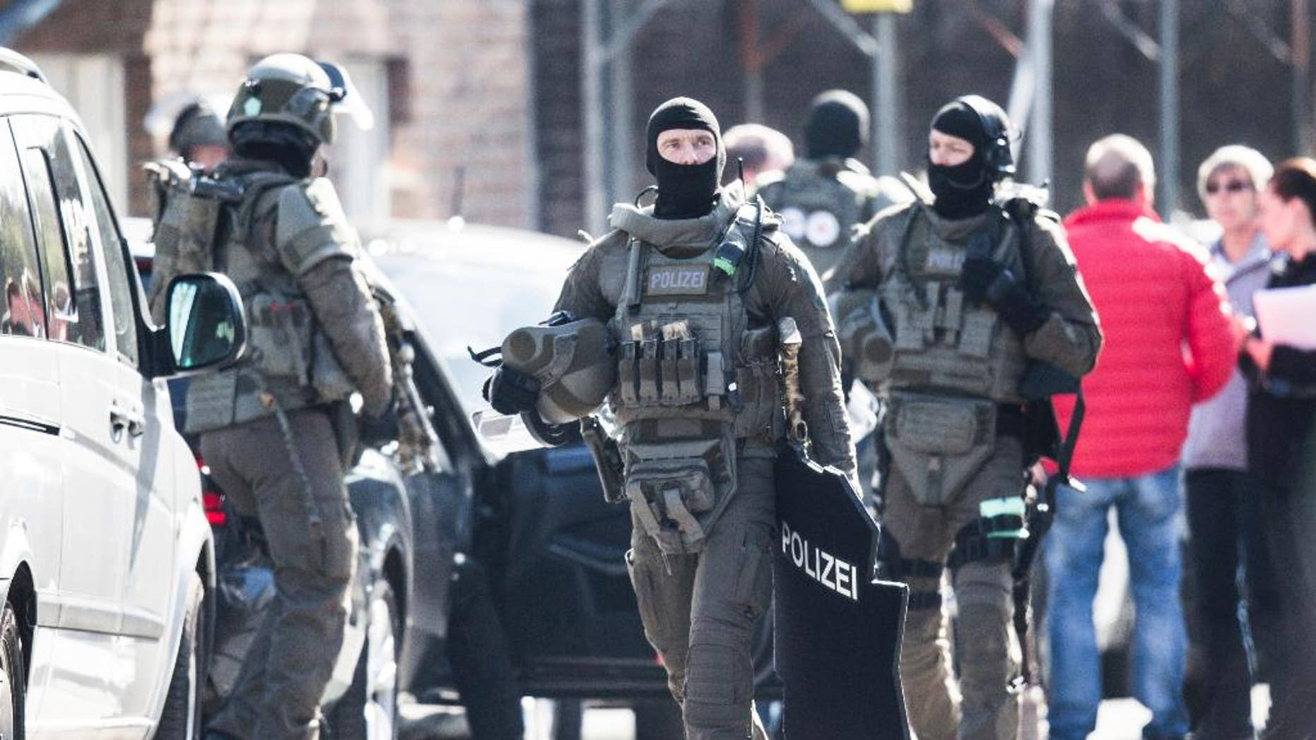 Officers of the special forces walk on a street in Duisburg, Germany, Thursday, March 16, 2017. An armed man robbed a bank on Thursday morning in Duisburg. According to first insights of the police, the man is still inside the building together with two employees. (Marcel Kusch/dpa via AP)