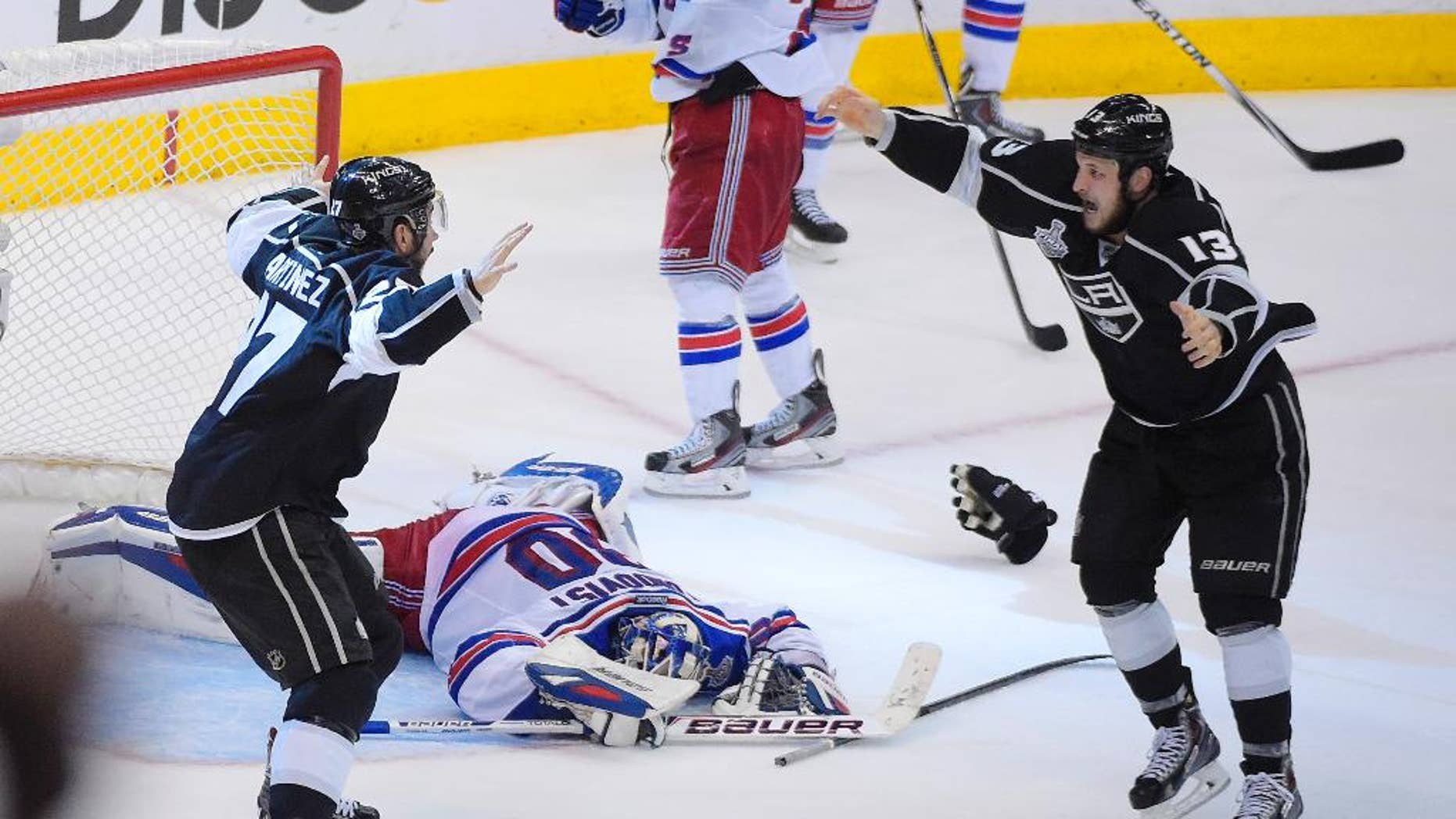 Los Angeles Kings defenseman Alec Martinez, left, celebrates after scoring the winning goal with Kyle Clifford, right, past New York Rangers goalie Henrik Lundqvist, of Sweden, during the second overtime period in Game 5 of an NHL hockey Stanley Cup finals, Friday, June 13, 2014, in Los Angeles.  (AP Photo/Mark J. Terrill)