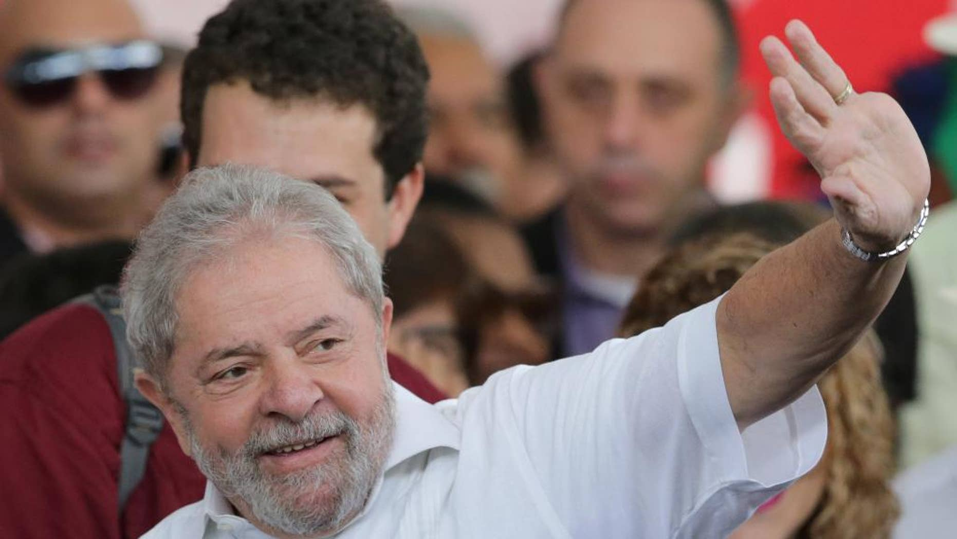 Brazil's former President Luiz Inacio Lula da Silva gestures to the crowd while arriving to a rally of Social Movements for Democracy, in a camp set up by supporters of President Dilma Rousseff in Brasilia, Brazil, Saturday, April 16, 2016. The lower chamber of Brazil's Congress on Friday began a debate on whether to impeach Rousseff, a question that underscores deep polarization in Latin America's largest country and most powerful economy. The crucial vote is slated for Sunday. (AP Photo/Eraldo Peres)