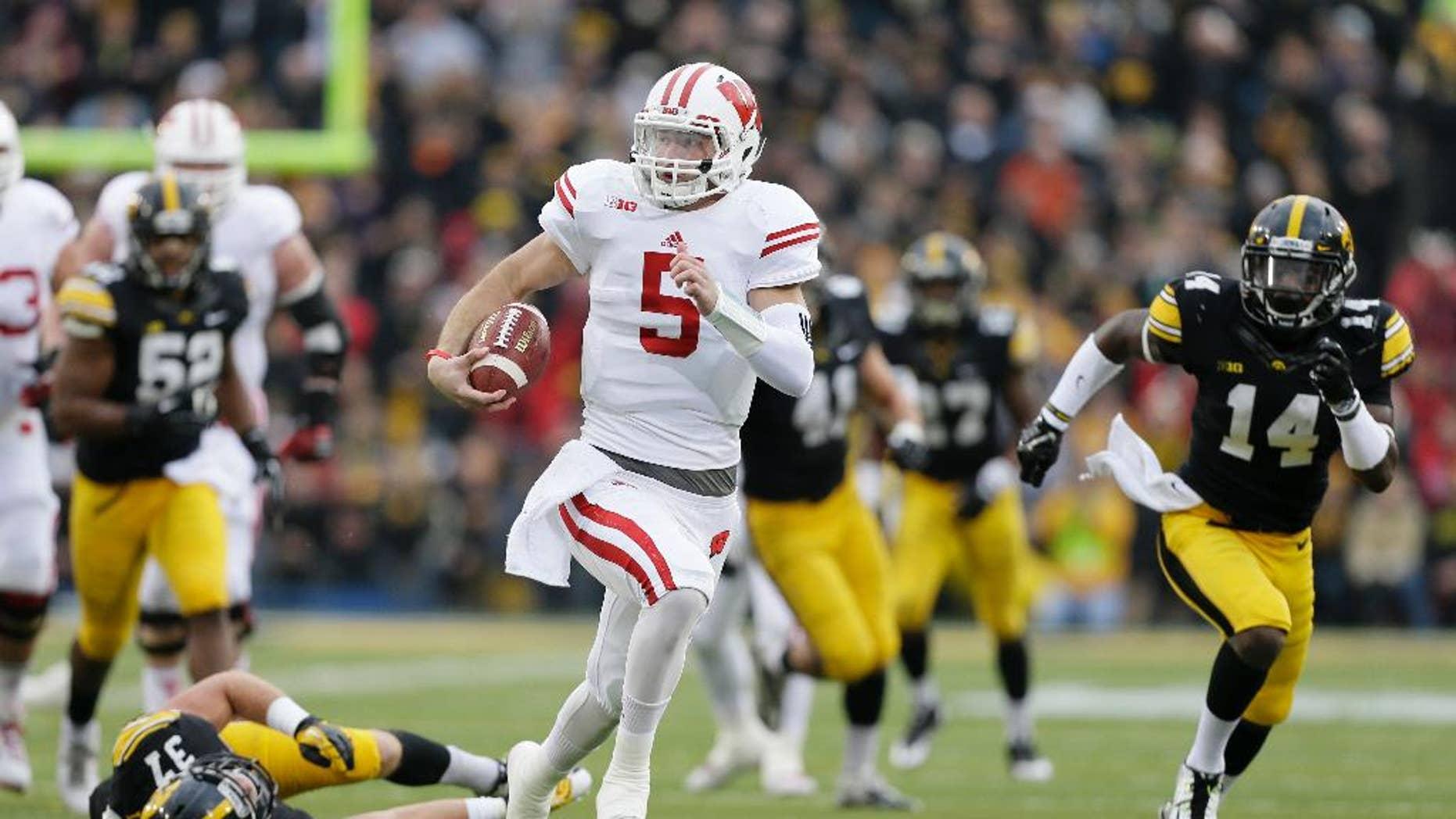 Wisconsin quarterback Tanner McEvoy (5) runs from Iowa defensive back John Lowdermilk (37) and defensive back Desmond King (14) during a 45-yard touchdown run in the first half of an NCAA college football game, Saturday, Nov. 22, 2014, in Iowa City, Iowa. (AP Photo/Charlie Neibergall)