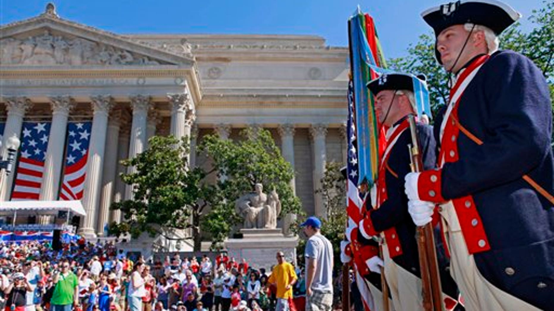 Soldiers with the 3rd U.S. Infantry Regiment Old Guard Continental Color Guard line up near the National Archives building, left, in Washington before the start of the Fourth of July, Independence Day, festivities Sunday, July 4, 2010. (AP Photo/Jacquelyn Martin)