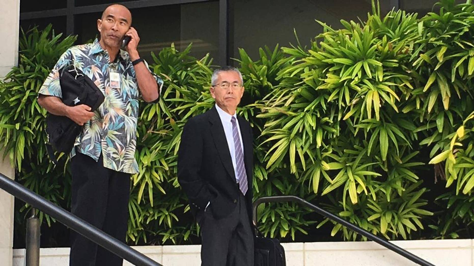 FILE- In this Nov. 1, 2016, file photo, Kauai Community Correctional Center Warden Neal Wagatsuma, left, uses a cellphone while walking out of U.S. District Court in Honolulu with Hawaii Deputy Attorney General Nelson Nabeta. After a week of deliberations, the jury on Tuesday, Dec. 20, voted unanimously in favor of defendants Neal Wagatsuma and the state of Hawaii in a lawsuit brought by a former jail social worker. (AP Photo/Jennifer Sinco Kelleher, File)