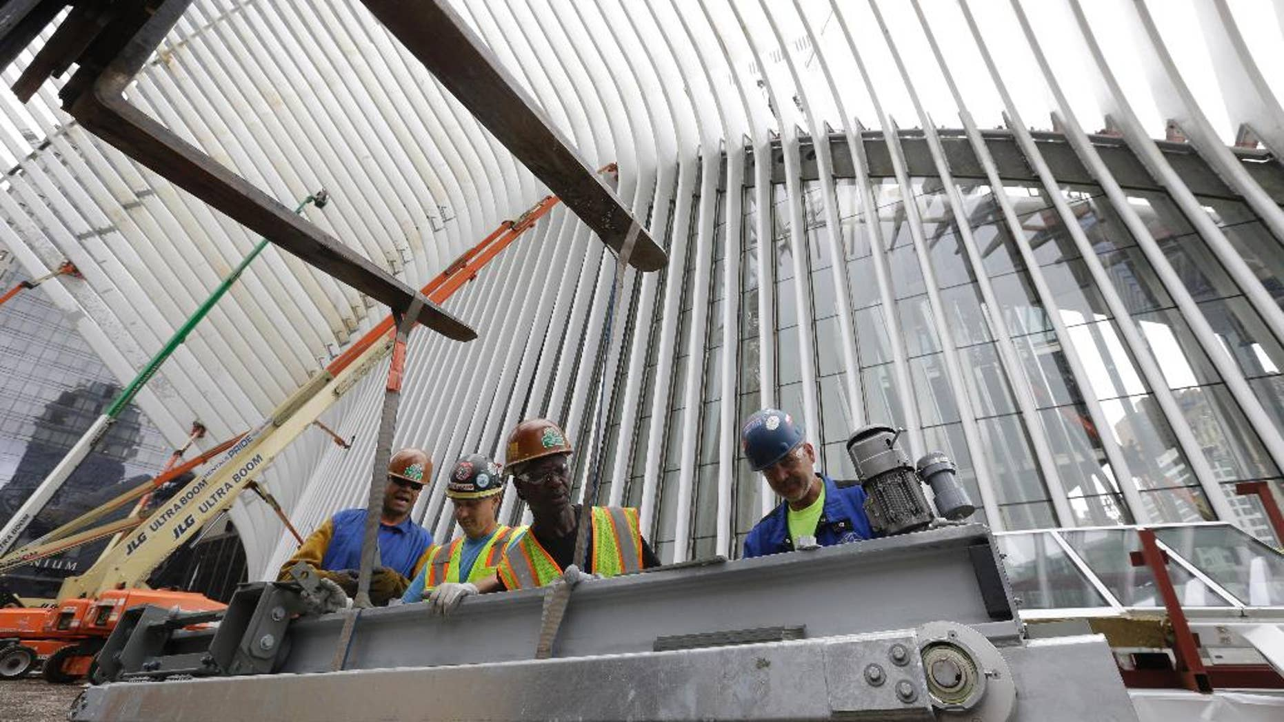 FILE - In this June 18, 2015, file photo, construction workers secure a steel apparatus to a crane that will be used on the roof of the Oculus structure at the World Trade Center transportation hub, in New York. The Commerce Department reports on U.S. construction spending in May on Wednesday, July 1, 2015. (AP Photo/Mary Altaffer, File)