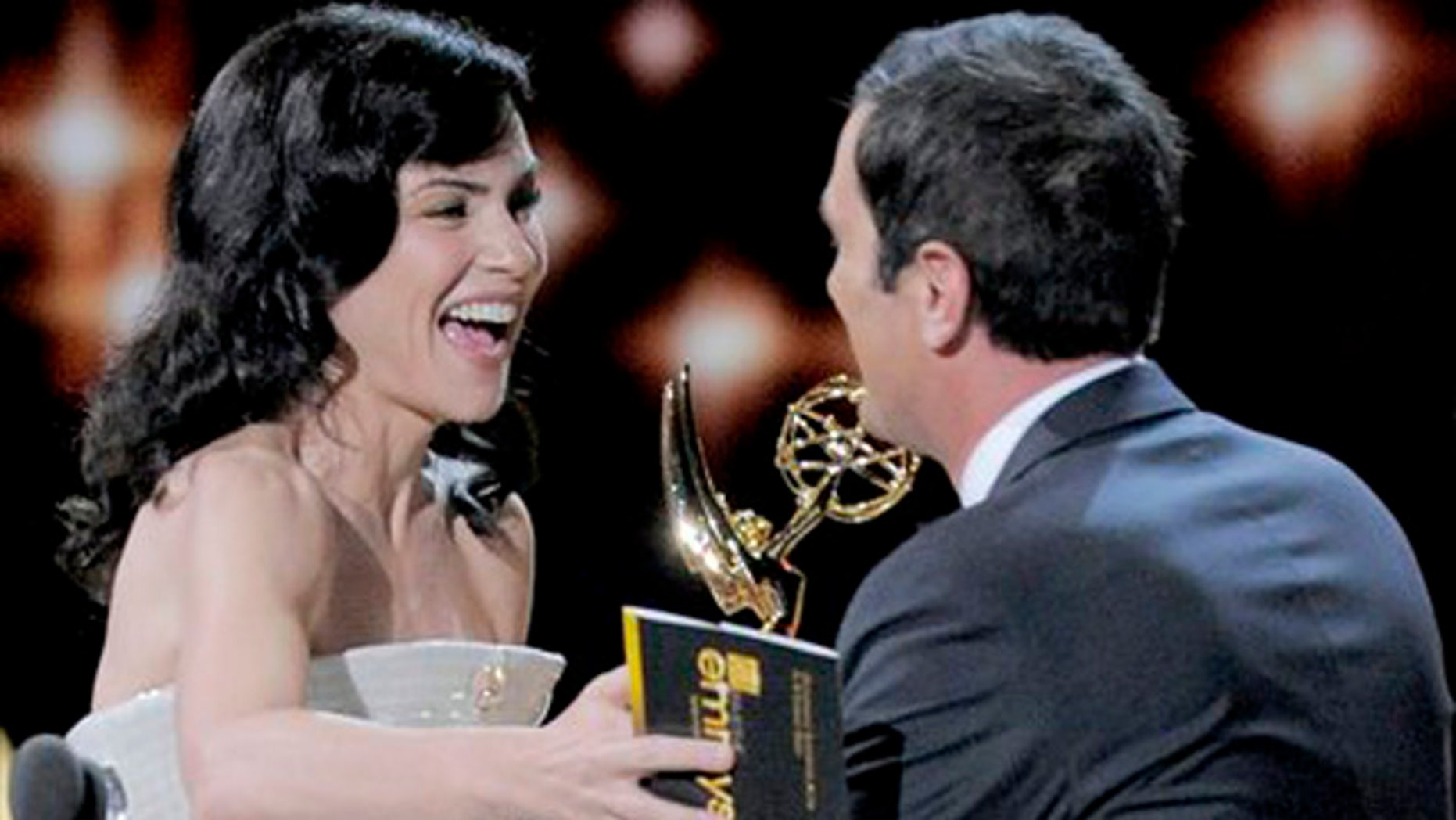 Ty Burrell, right, accepts the award for outstanding supporting actor in a comedy series for Modern Family from presenter Julianna Margulies at the 63rd Primetime Emmy Awards on Sunday, Sept. 18, 2011 in Los Angeles.