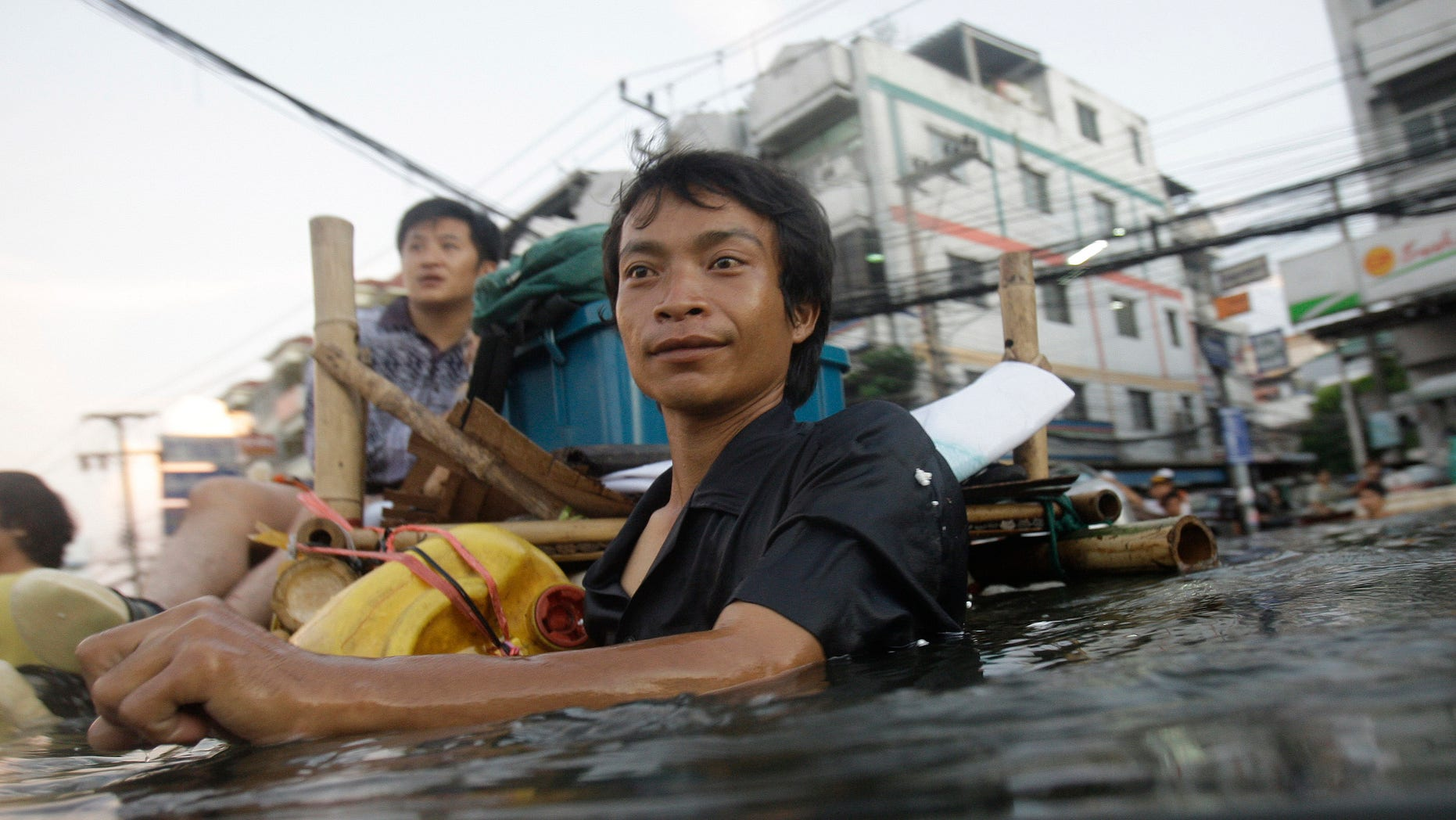 Oct. 27, 2011: A Thai man wades along chest-deep floodwaters in the outskirts of Bangkok, Thailand.
