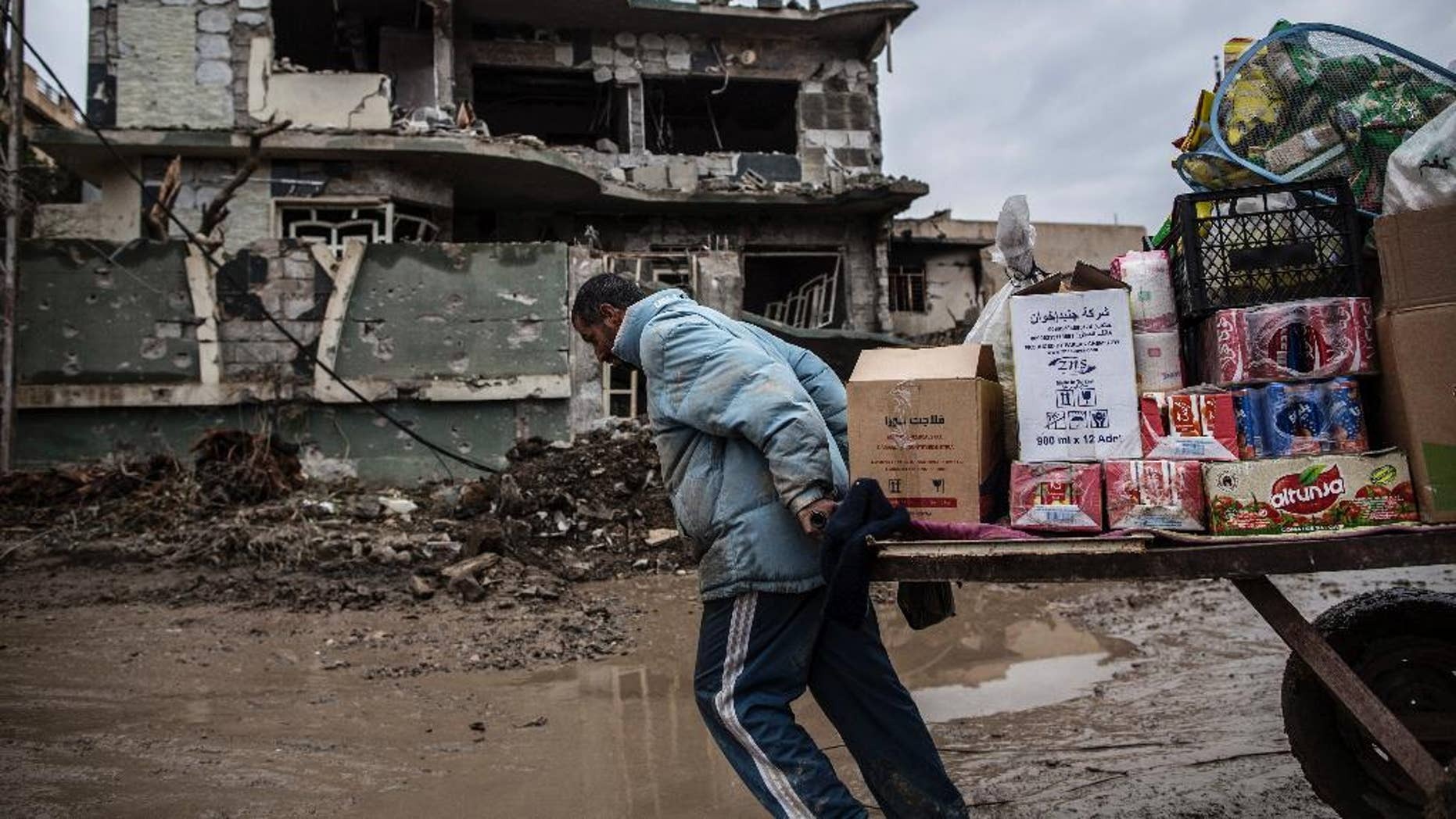 A street vendor pulls his cart in front of a house damaged by the fight in Mishraq district in Mosul, Iraq, Tuesday, Dec. 20, 2016. Advancing into Mosul has become a painful slog for Iraqi forces. Islamic State group militants have fortified each neighborhood, unlike past battles where they concentrated their defenses in one part of the city. (AP Photo/Manu Brabo)