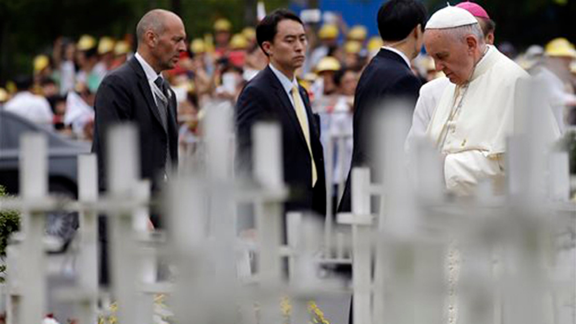 """Pope Francis prays in front of white wooden crosses of the unborn children garden during his visit to the """"House of Hope"""" center for disabled in Kkottongnae, South Korea, Saturday, Aug. 16, 2014. Francis bowed his head in prayer before the monument and spoke with an anti-abortion activist with no arms and no legs. (AP Photo/Gregorio Borgia)"""