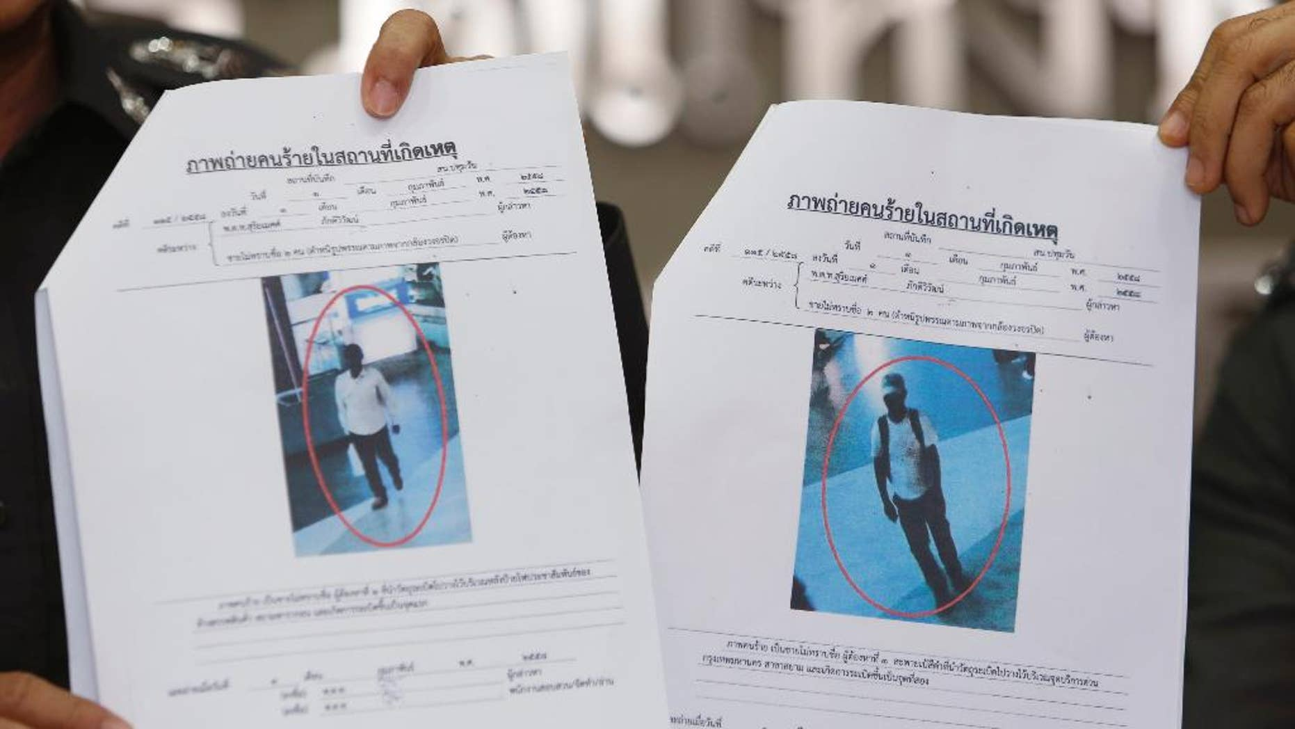 """Photos of two suspects believed linked to a pair of small bomb blasts outside a luxury shopping mall in Bangkok over the weekend, are shown by police officers at the police headquarters in Bangkok, Thailand Wednesday, Feb. 4, 2015. Authorities in Thailand have issued arrest warrants for the two suspects. The blurry images of the suspects, described as """"Asian-looking"""" by a police spokesman, were captured on closed-circuit camera footage close to where the homemade pipe bombs detonated and wounded one person. (AP Photo/Sakchai Lalit)"""