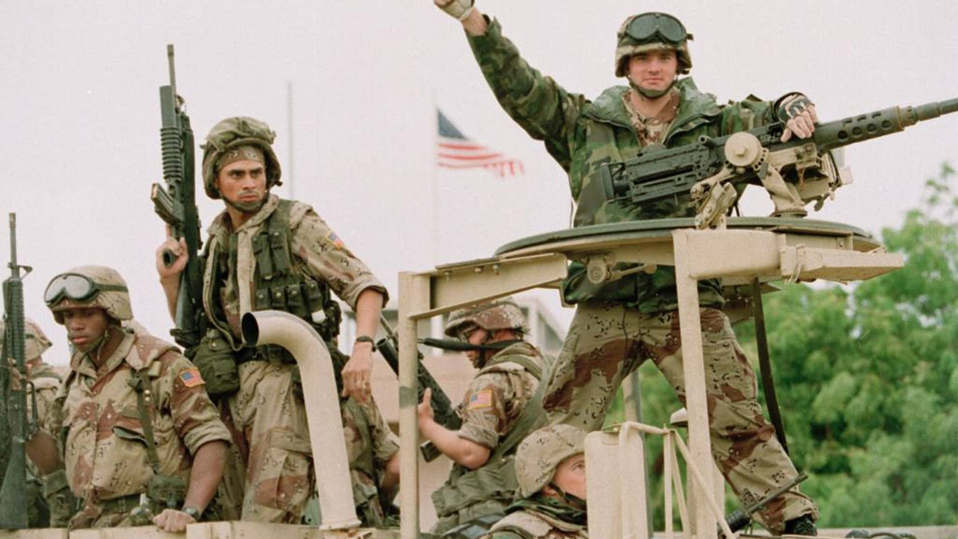 FILE - In a Dec. 10, 1992 file photo, a U.S. Marine gives the thumbs up as a truck load of troops arrive at the reopened U.S. Embassy in Mogadishu, Somalia.  According to the U.S. Africa Command on Friday April 14, 2017,  the U.S. military is sending dozens of regular troops to Somalia to train Somali soldiers in the largest such deployment to the Horn of Africa country in roughly two decades.   (AP Photo/Denis Pauqin, File)