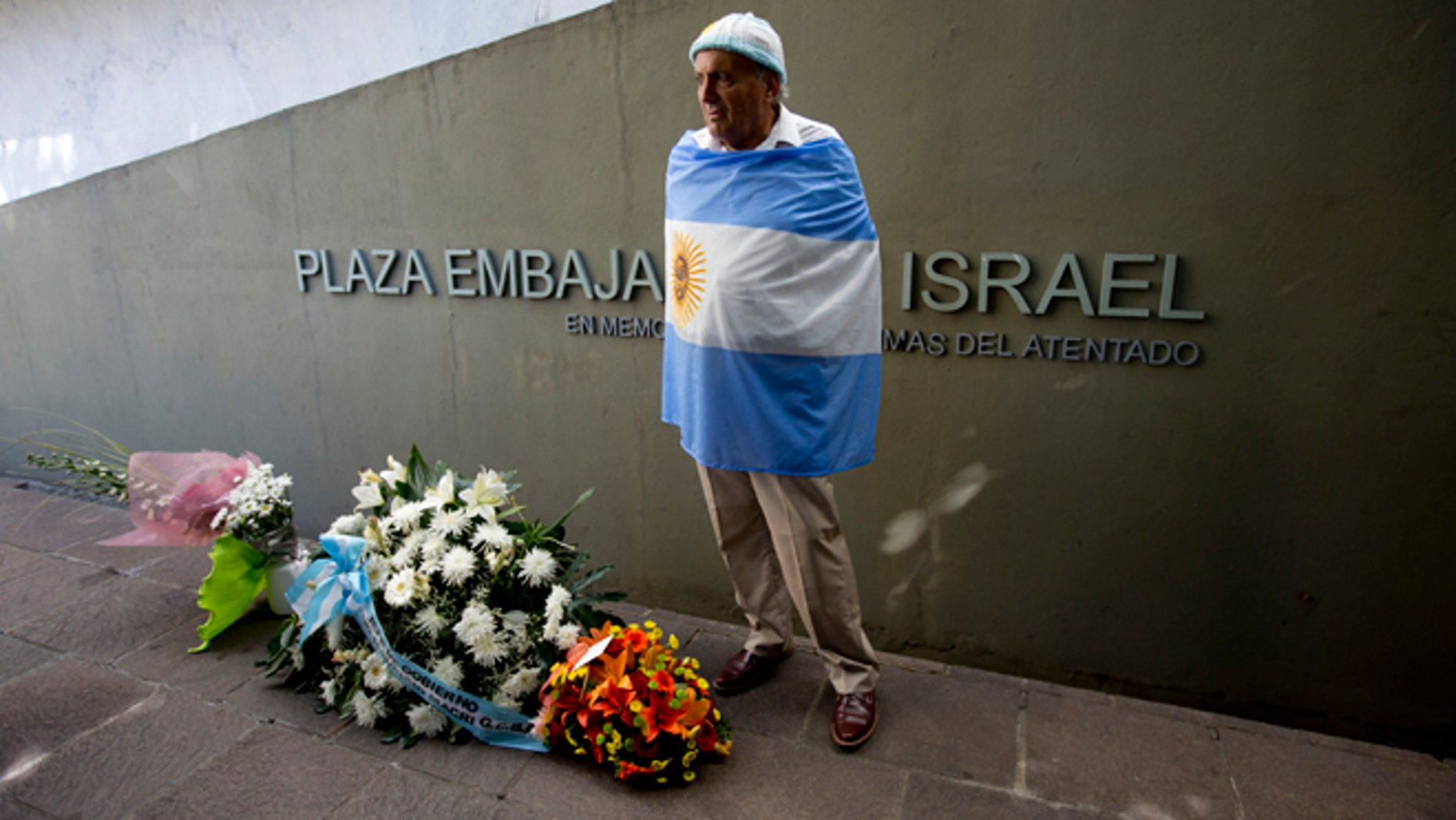 Juan Pulvirenti stands next to several floral arrangements placed on the site where the Israeli Embassy used to be during an act to commemorate the 23rd anniversary of the bomb attack that destroyed the building killing 22 people, in Buenos Aires, Argentina, Tuesday, March 17, 2015. (AP Photo/Natacha Pisarenko)