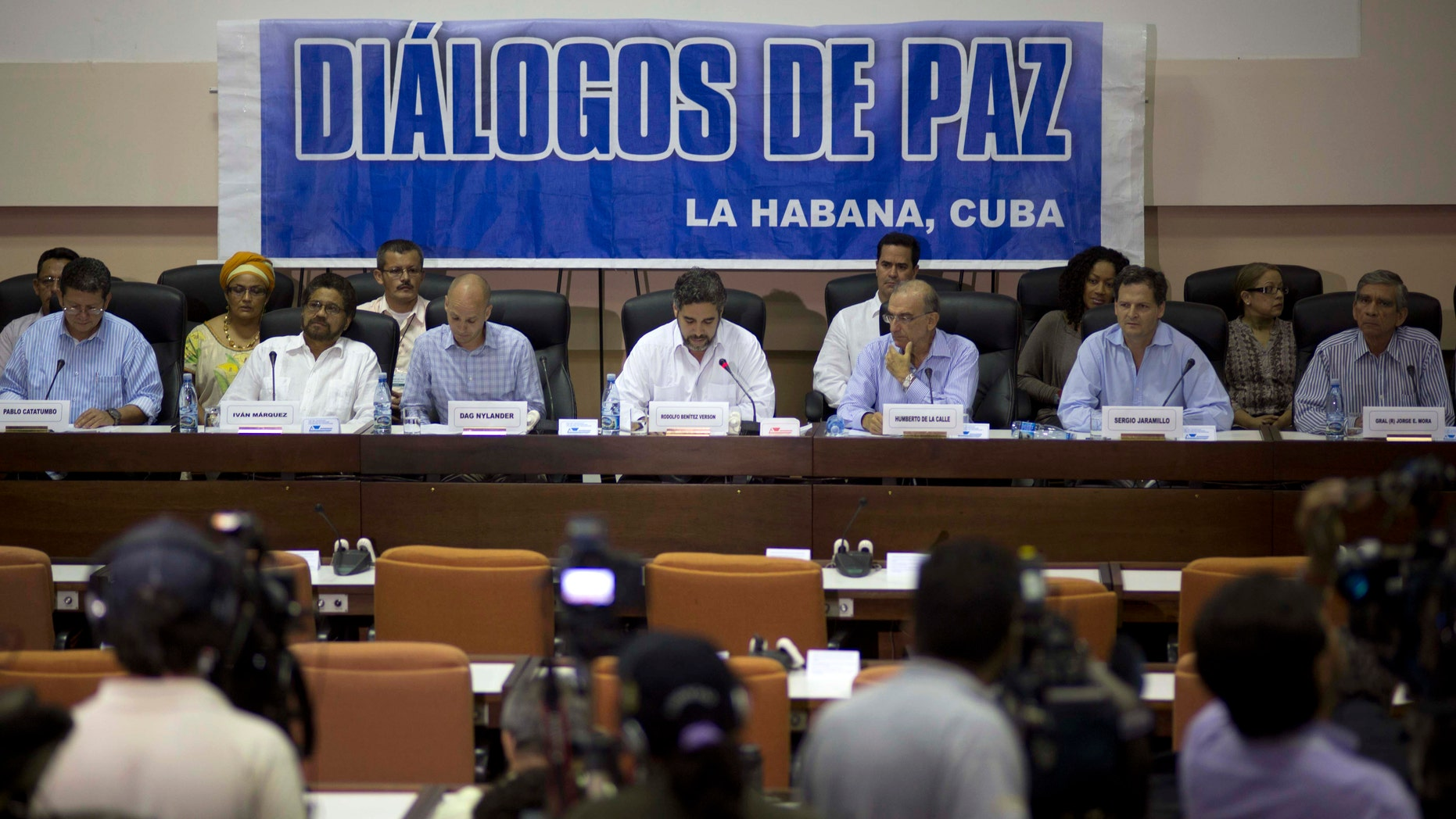 """FILE - In this May 16, 2014 file photo, negotiators from the Revolutionary Armed Forces of Colombia (FARC), left, and Colombia's government, right, give a press conference under a sign that reads in Spanish """"Peace Talks"""" in Havana, Cuba. Colombia's government has rebuffed a unilateral truce declared on Wednesday, Dec. 18, 2014 by the country's largest rebel group, saying conditions demanded by the guerrillasâ are unacceptable until a peace deal is reached. Sitting at the table, from left, are chief of the western bloc of the FARC Pablo Catatumbo, FARC chief negotiator Ivan Marquez, Norwegian guarantor Dag Nylander, Cuban guarantor Rodolfo Benitez Verson, head of Colombia's government team Humberto de la Calle, government negotiator Sergio Jaramillo, and government negotiator Gen. Jorge Mora. (AP Photo/Ramon Espinosa, File)"""