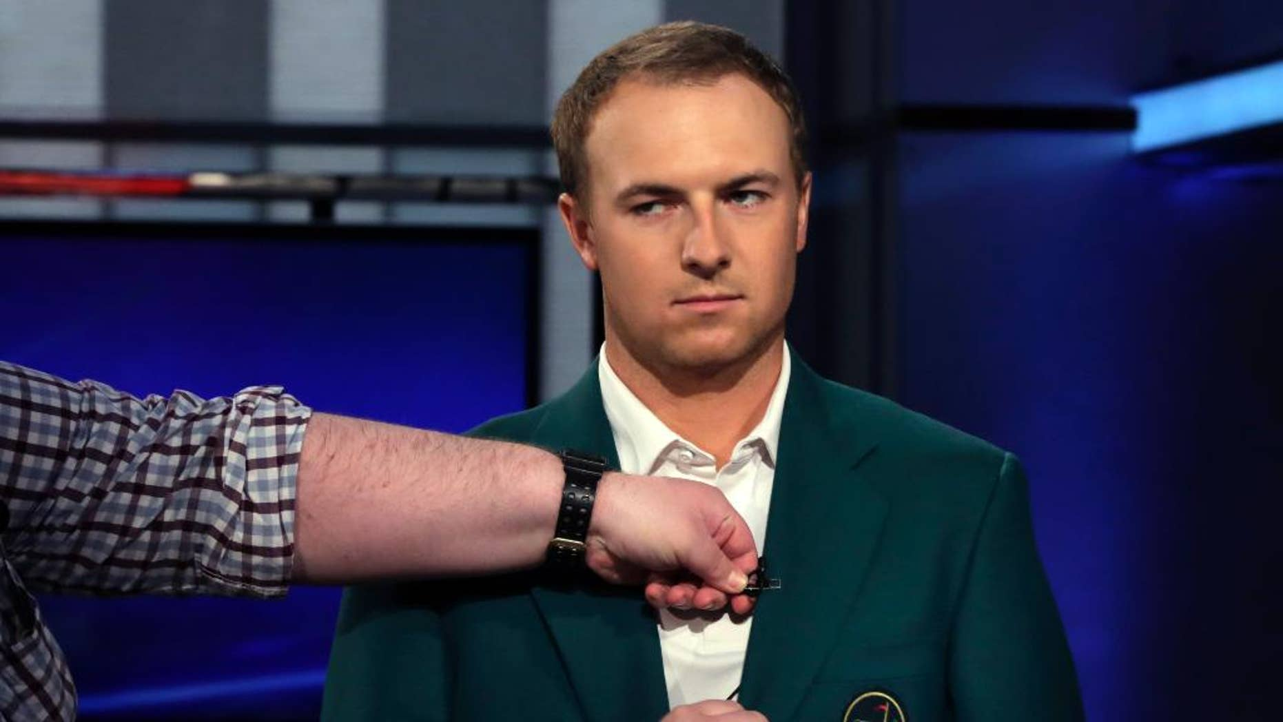 "Masters golf champion Jordan Spieth has his microphone attached to the lapel of his green jacket before his interview during the ""After the Bell"" television program, on the Fox Business Network,  Tuesday, April 14, 2015, in New York. Nothing annoys the 21-year-old more than a nickname some players have given him — Golden Child. (AP Photo/Richard Drew)"