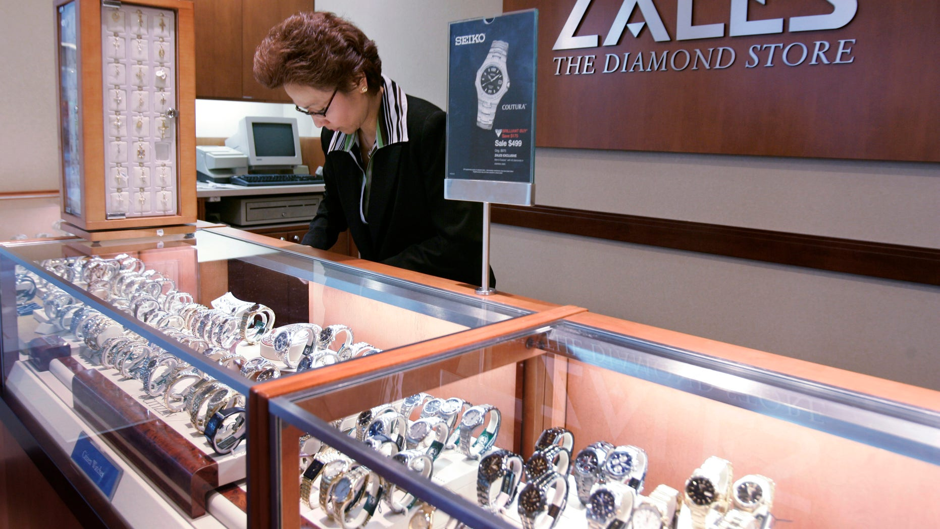 FILE - In this Jan. 4, 2007, a Zales jewelry store worker looks at watches in San Bruno, Calif.  Signet Jewelers is buying Zale Corp. for approximately $690 million to help diversify its business and expand further internationally. Shares of Zale soared more than 39 percent in Wednesday, Feb. 19, 2014,  premarket trading, while Signet Jewelers Ltd.' stock rose more than 9 percent.  (AP Photo/Paul Sakuma, file)