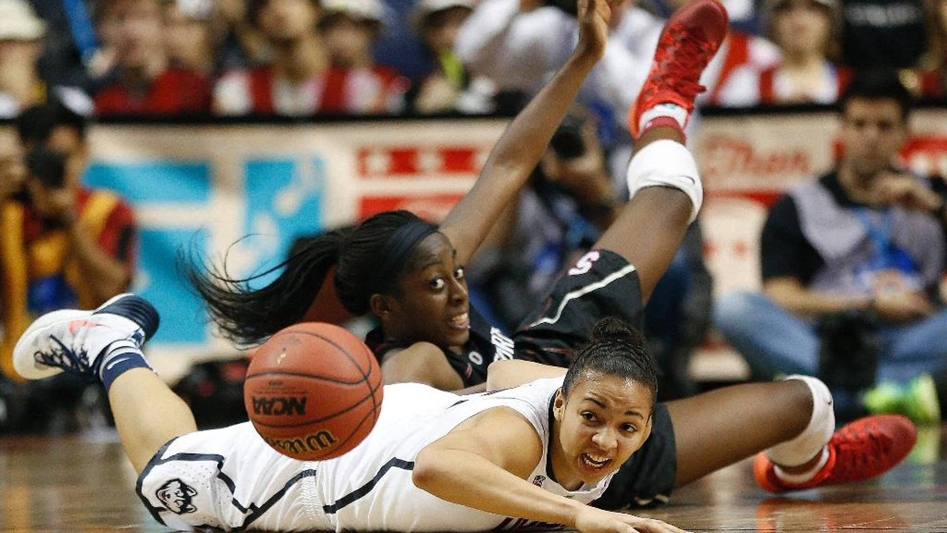 Stanford forward Chiney Ogwumike (13) and Connecticut guard Bria Hartley (14) collide during the second half of the semifinal game in the Final Four of the NCAA women's college basketball tournament, Sunday, April 6, 2014, in Nashville, Tenn. Connecticut won 75-56. (AP Photo/John Bazemore)