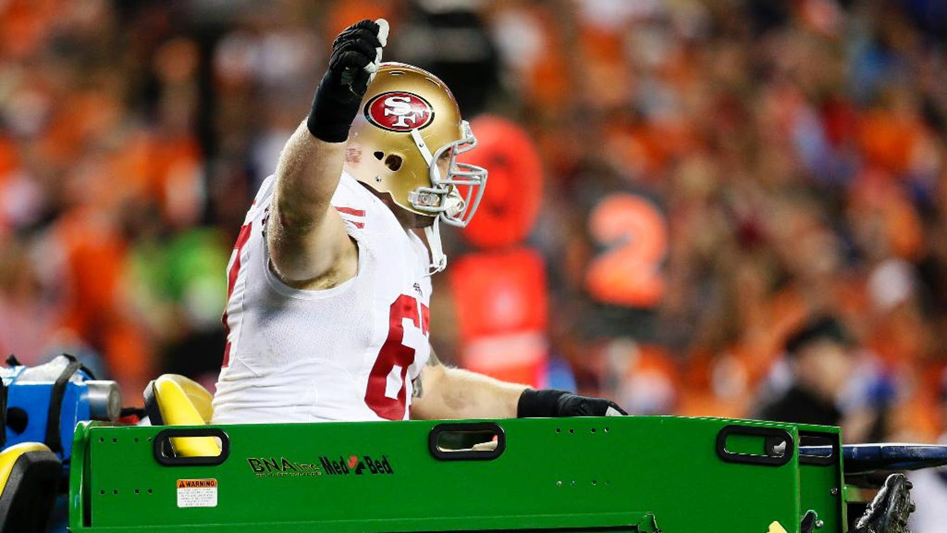 San Francisco 49ers center Daniel Kilgore gives the thumbs up as he is carted off the field against the Denver Broncos during the second half of an NFL football game, Sunday, Oct. 19, 2014, in Denver.  (AP Photo/Joe Mahoney)