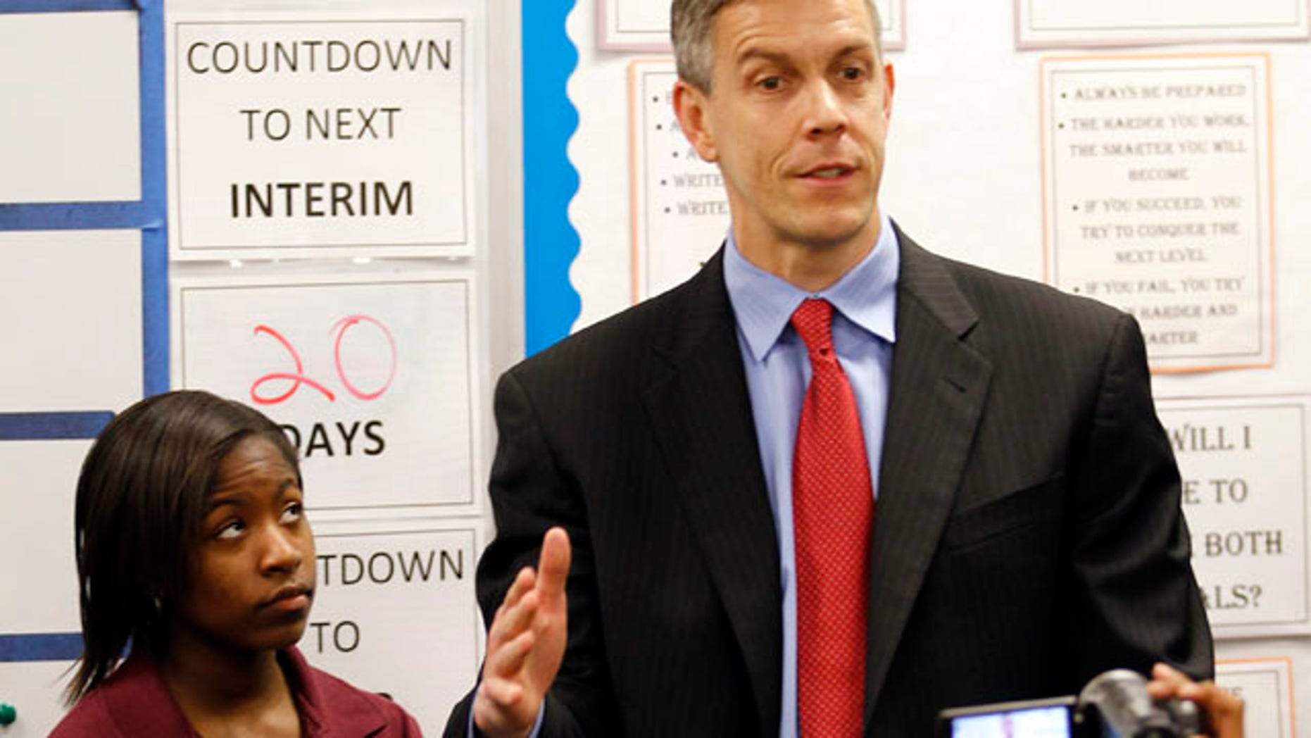 FILE - In this April 15, 2011 file photo, student Faith Brown, left, listens as U.S. Department of Education Secretary Arne Duncan speaks to students during tour the Charles A. Tindley Accelerated School in Indianapolis. Duncan says he will announce a new waiver system Monday, Aug. 8, 2011, to give schools a break from student testing mandates in the federal No Child Left Behind law. (AP Photo/Michael Conroy, File)