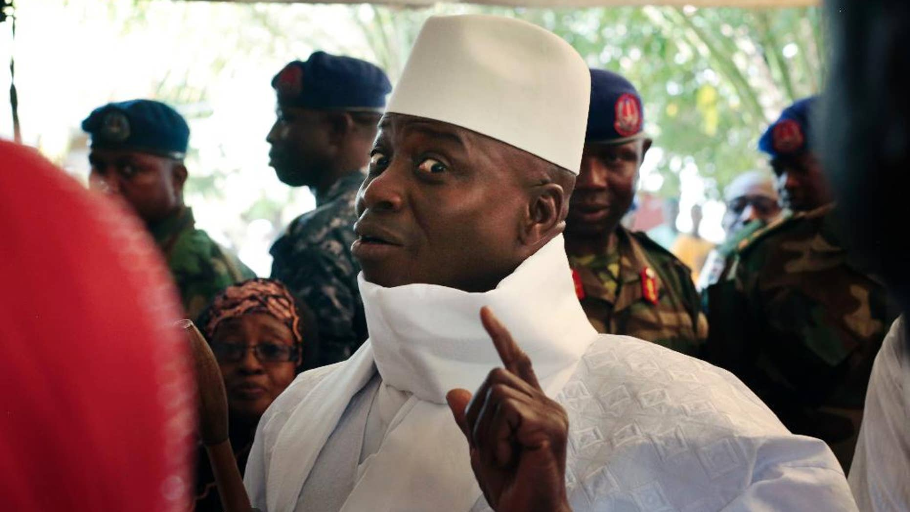 FILE- In this Thursday, Dec. 1, 2016 file photo, Gambia's president Yahya Jammeh shows his inked finger before voting in Banjul, Gambia. President Yahya Jammeh, who at first surprised Gambians by conceding defeat after 22 years in power, a week later announced that he had changed his mind. He alleges voting irregularities that make the Dec. 1 ballot invalid. (AP Photo/Jerome Delay, File)