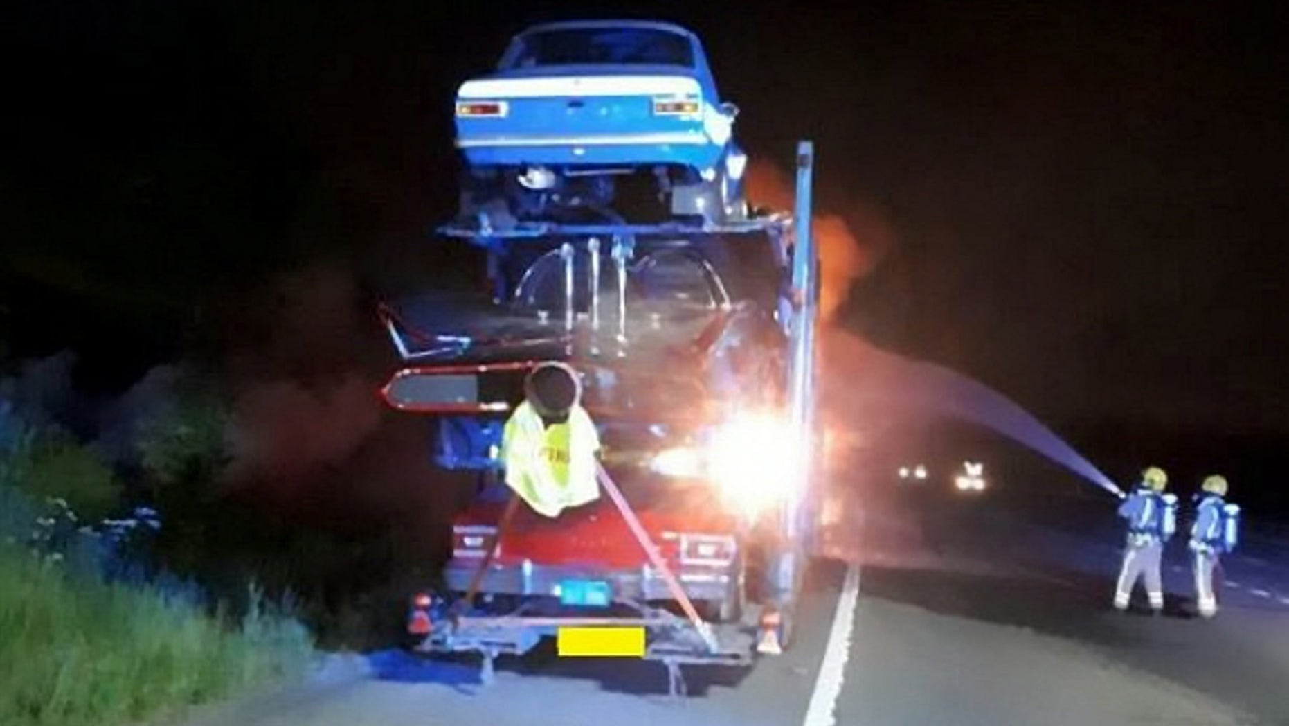 A transporter carrying a dozen novelty cars including a BATMOBILE caught fire - burning a number of vintage vehicle to bits. See SWNS story SWFIRE; The lorry was travelling westbound on the M4 near Bath on Wednesday night when it went up in flames. Highways England was forced to shut two lanes of the motorway as firefighters battled the blaze into the early hours of Thursday. It is not know the extent of damage the cars suffered, but Highways England said a number of the specialists cars along with the transporter cab had been destroyed. The truck had been transporting a number of classic cars including a 'Dukes of Hazzard' General Lee, Batmobile, 'Transformers' Ford Mustang and 'Starsky and Hutch' Ford Torino.