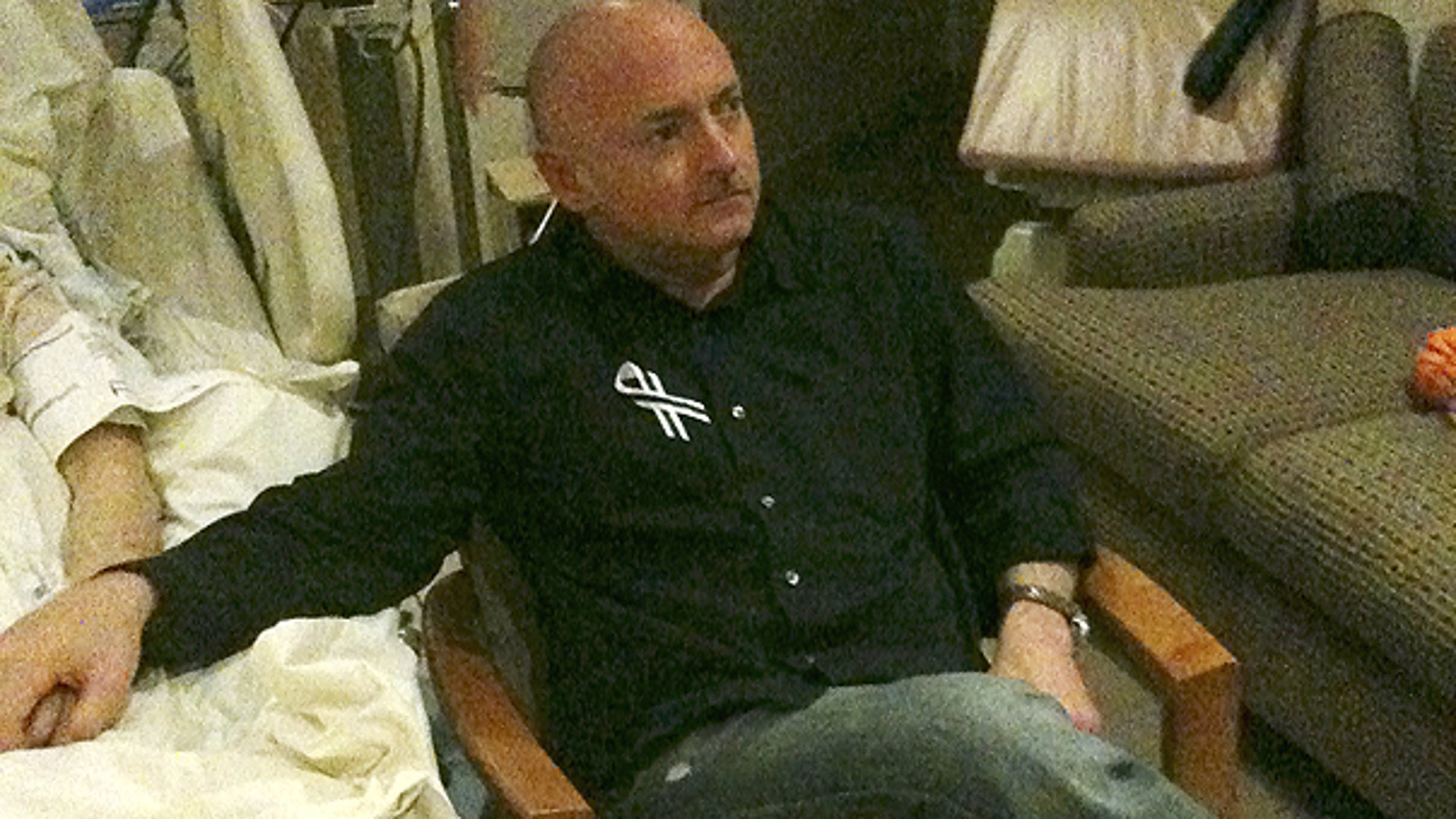 Jan. 25: A photo released by the office of U.S. Rep. Gabrielle Giffords shows Rep. Giffords husband Mark Kelly watching the State of The Union speech while holding his wife's hand in her hospital room in Houston.