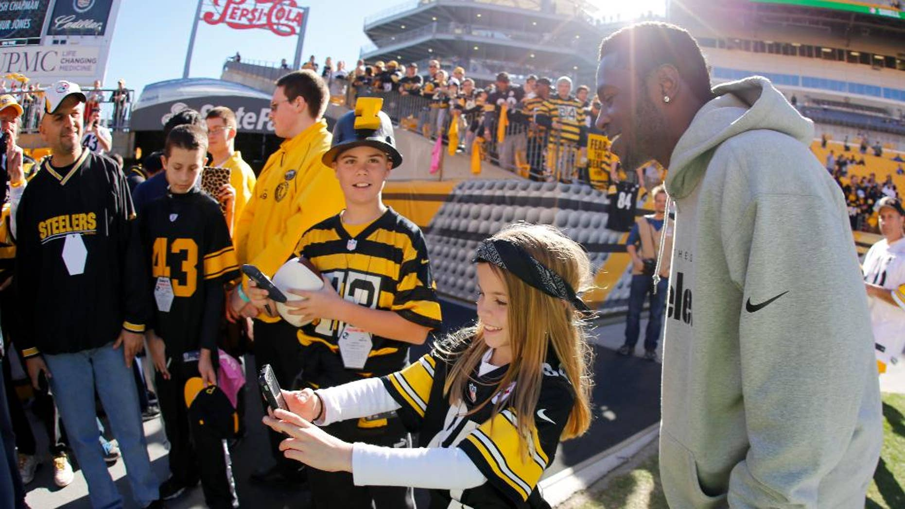 Pittsburgh Steelers wide receiver Antonio Brown, right, has his photo taken with fans during warmups before an NFL football game against the Indianapolis Colts, Sunday, Oct. 26, 2014, in Pittsburgh. (AP Photo/Gene Puskar)