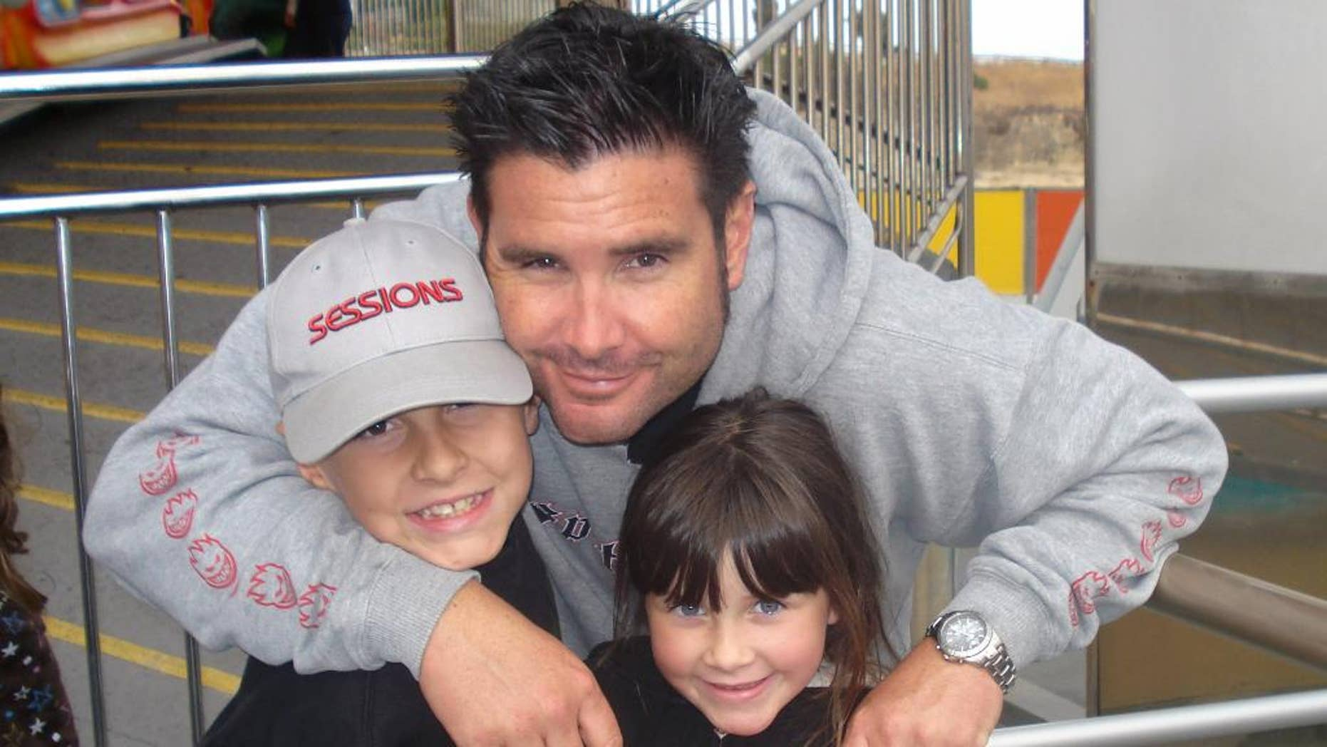 FILE - This undated file photo provided Tuesday April 5, 2011 by John Stow shows Bryan Stow holding his 12-year-old son and 8-year-old daughter. Stow who suffered a traumatic brain injury after being beaten by two Dodger fans put up his hands and fingers, fist bumped his mom and talked about his goals in a new interview three years after the attack outside Dodger Stadium. Stow, wearing a Giants tank top, spoke to ESPN on Tuesday, Oct. 21, 2014 from his parents' home in the Northern California city of Capitola, where he watched Game 1 of the World Series between the Giants and Kansas City Royals. (AP Photo/John Stow, File)