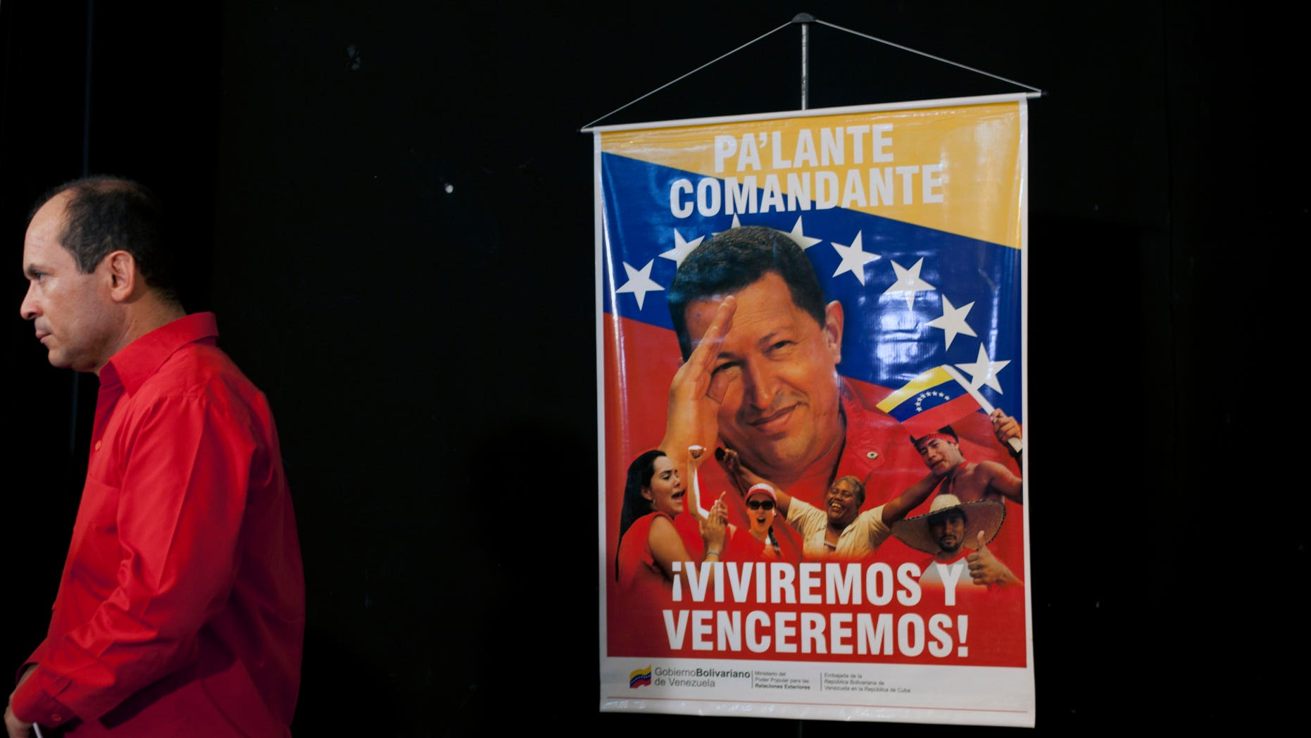 """A poster of Venezuela's President Hugo Chavez that reads """"Move forward commander, we will live and overcome"""" hangs as Venezuela's ambassador to Cuba Edgardo Antonio Ramirez stands by after a press conference by Cuban artists and intellectuals to show support for Chavez in Havana, Cuba, Monday, Jan. 7, 2013. Chavez hasn't spoken or appeared publicly since his Dec. 11 operation in Cuba, his fourth surgery for an undisclosed type of pelvic cancer. Speculation about the leader's condition has grown since the operation. (AP Photo/Ramon Espinosa)"""