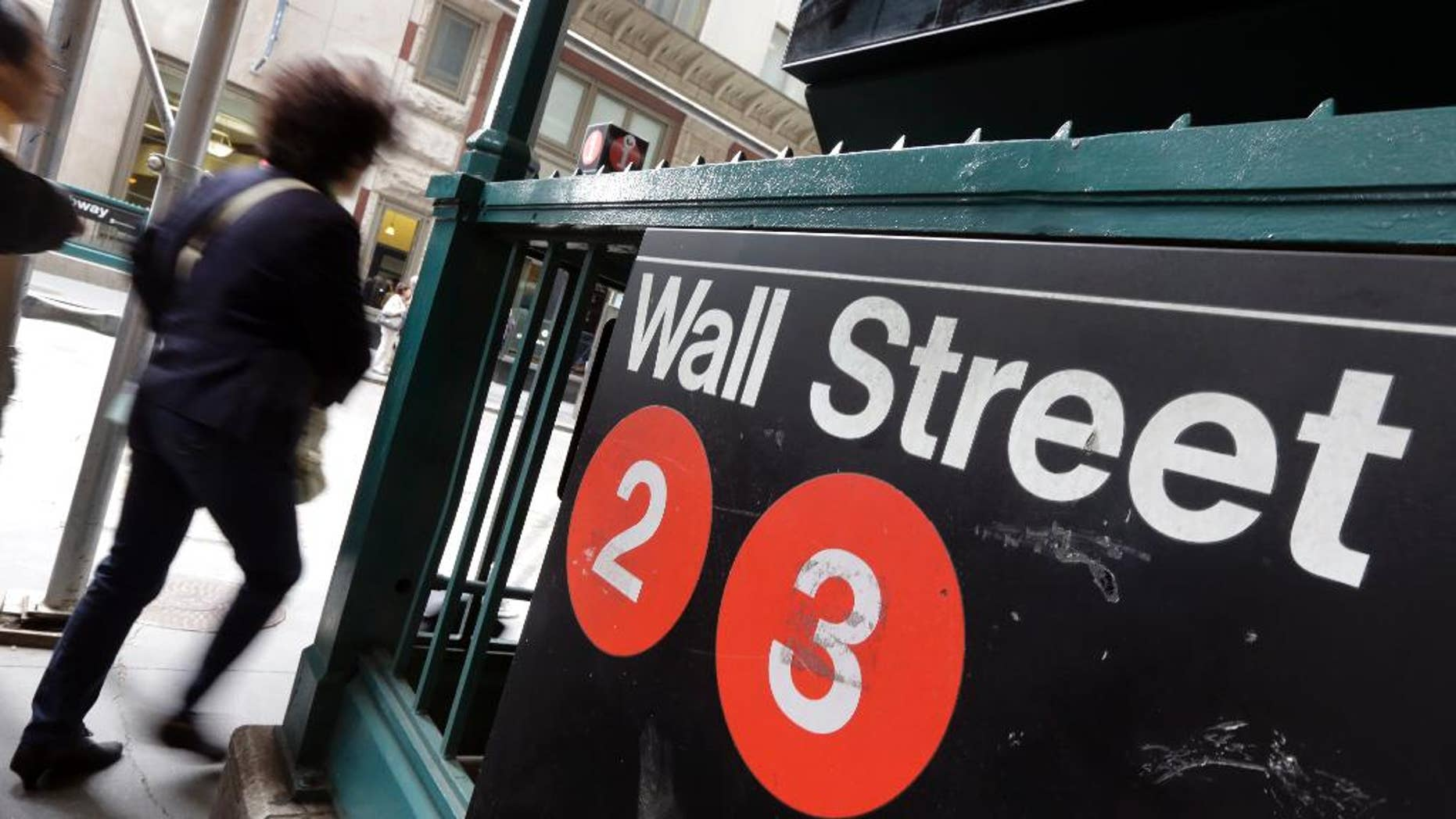 FILE - In this Oct. 2, 2014 file photo, people pass a Wall Street subway stop, in New York's Financial District. U.S. stocks moved lower in early trading Tuesday, March 31, 2015, erasing some gains from the day before. (AP Photo/Richard Drew, File)