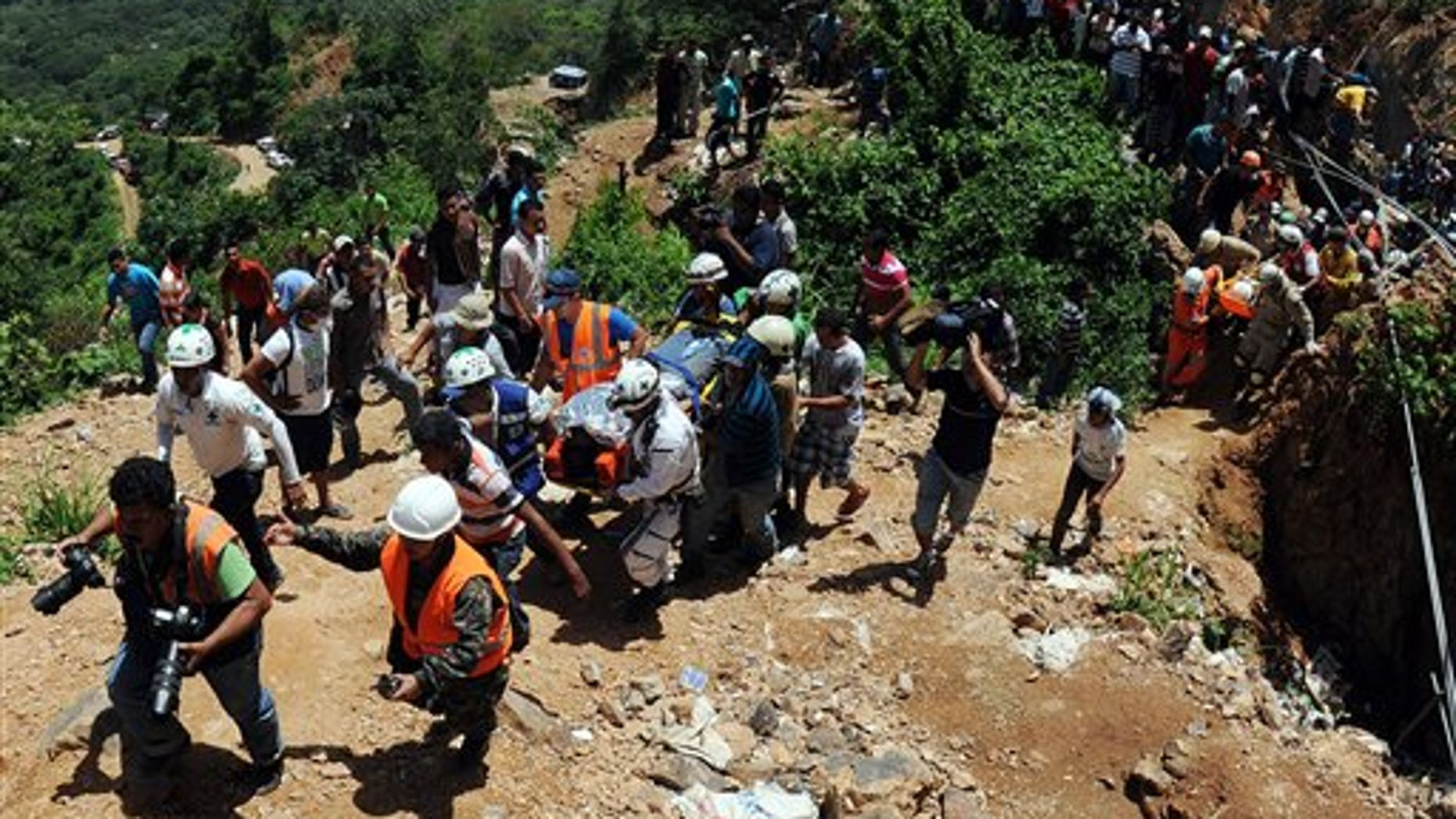 Rescue workers carry a miner who was trapped in a gold mine after a landslide in San Juan Arriba, Choluteca in southern Honduras, Friday July 4, 2014. Three miners were rescued Friday after spending more than two days trapped following a collapse at a small, wildcat gold mine. Eight others remain missing. (AP Photo/Fernando Antonio)