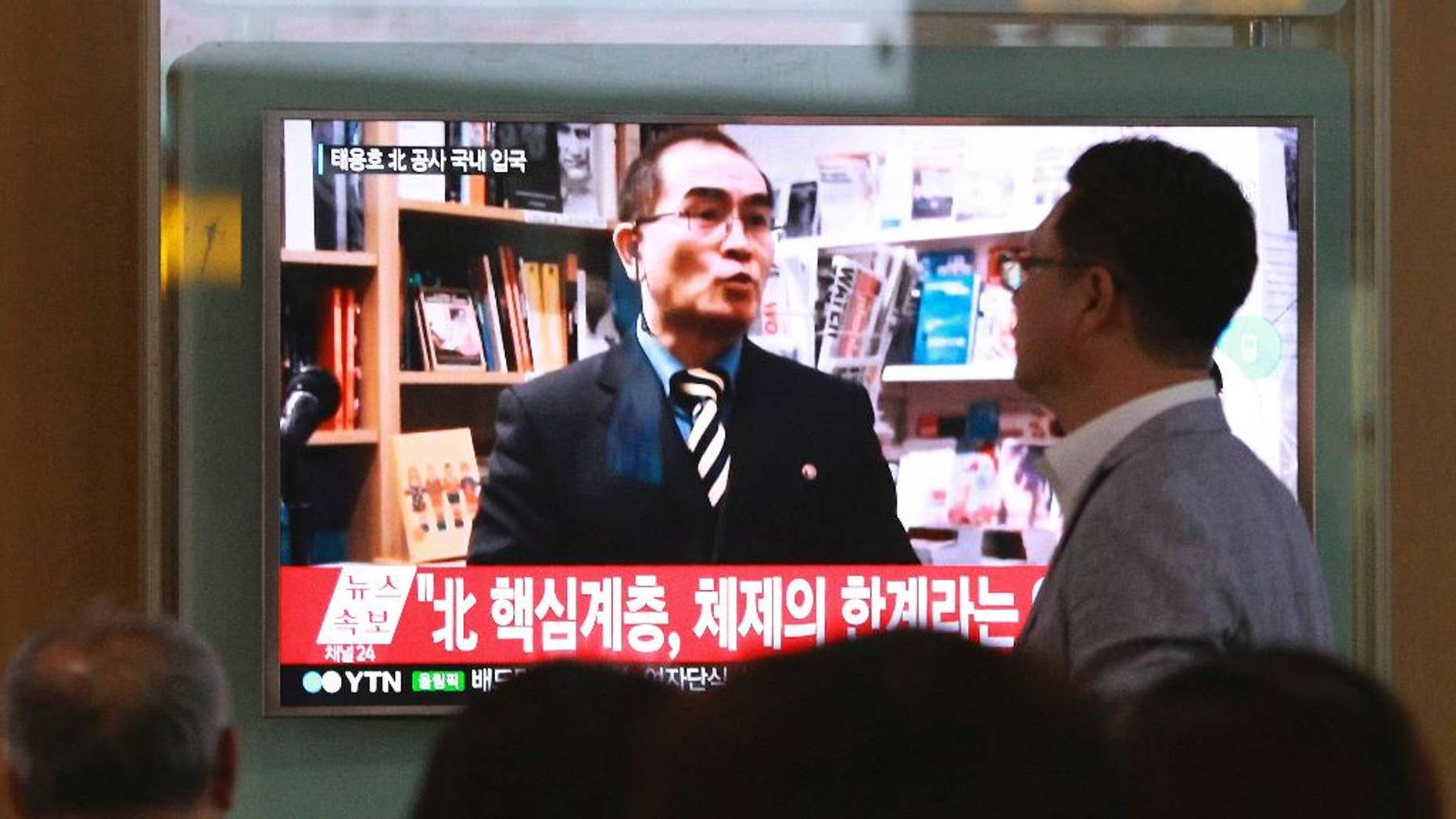 "FILE - In this Aug. 17, 2016 file photo, people watch a TV news program showing a file image of Thae Yong Ho, a high-profile North Korean defector, at Seoul Railway Station in Seoul, South Korea. Thae told on Monday, Dec. 19, 2016, South Korean lawmakers that he decided to flee because of disillusionment with what he describes as a ""tyrannical reign of terror"" by leader Kim Jong Un. The letters read ""A high-ranking North Korean diplomat."" (AP Photo/Ahn Young-joon, File)"