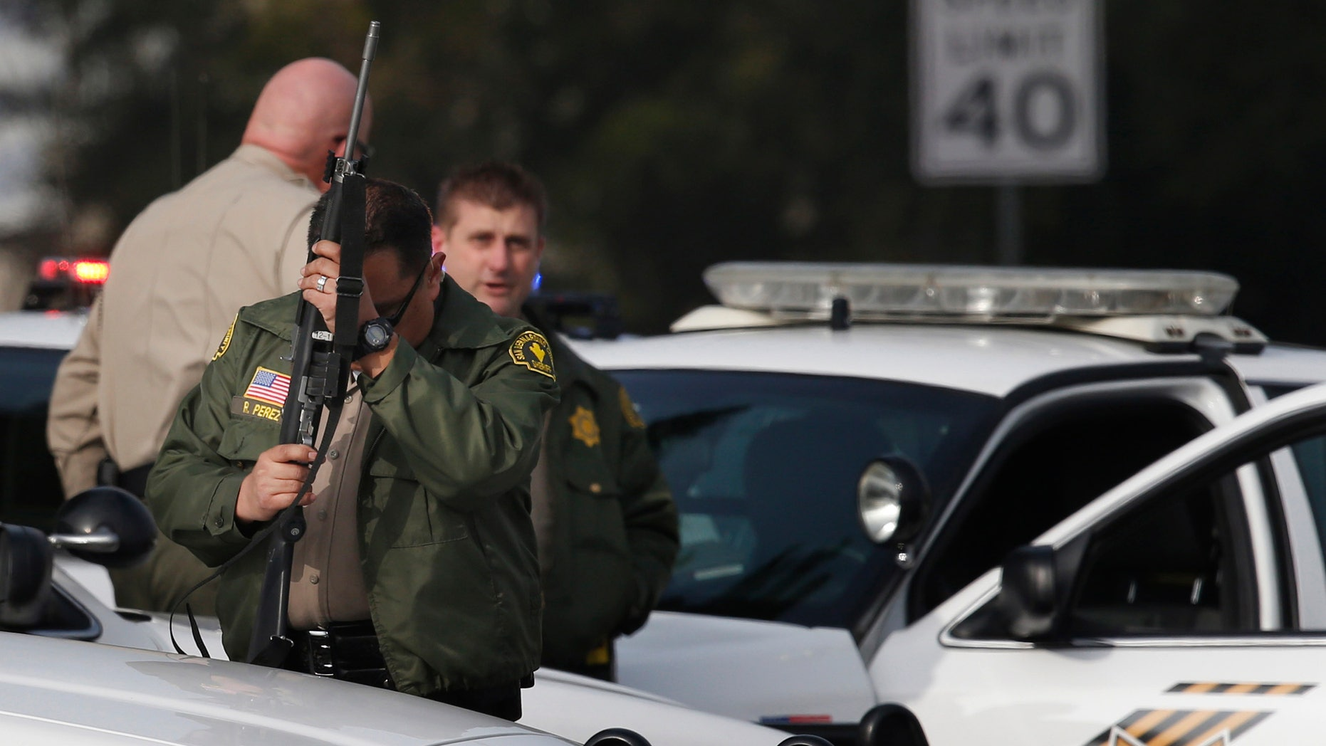A San Bernardino County sheriff's deputy stands guard near the area where a shooting took place in Riverside, Calif, Thursday, Feb. 7, 2013. Police launched a massive manhunt for a former Los Angeles officer suspected of going on a killing spree, slaying a couple over the weekend, opening fire on two Los Angeles officers early Thursday and then ambushing two other police officers, killing one. (AP Photo/Jae C. Hong)