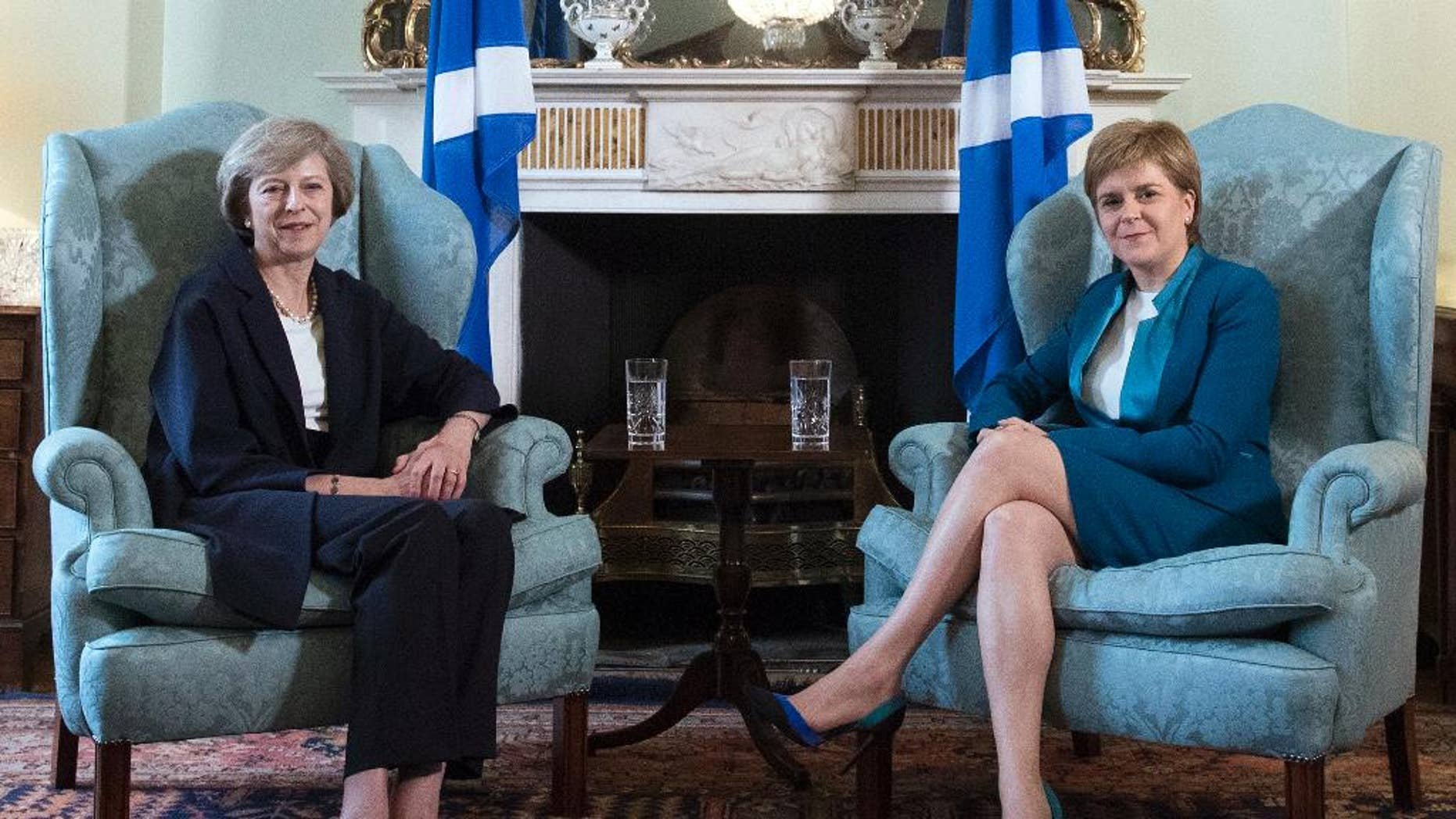 """Britain's new Prime Minister Theresa May, left, meets with First Minister of Scotland, Nicola Sturgeon at Bute House in Edinburgh, Scotland, Friday July 15, 2016, with Scottish saltire flags behind.  Prior to the meeting, May said """"This visit to Scotland is my first as prime minister and I'm coming here to show my commitment to preserving this special union that has endured for centuries."""" (Pool via AP)"""