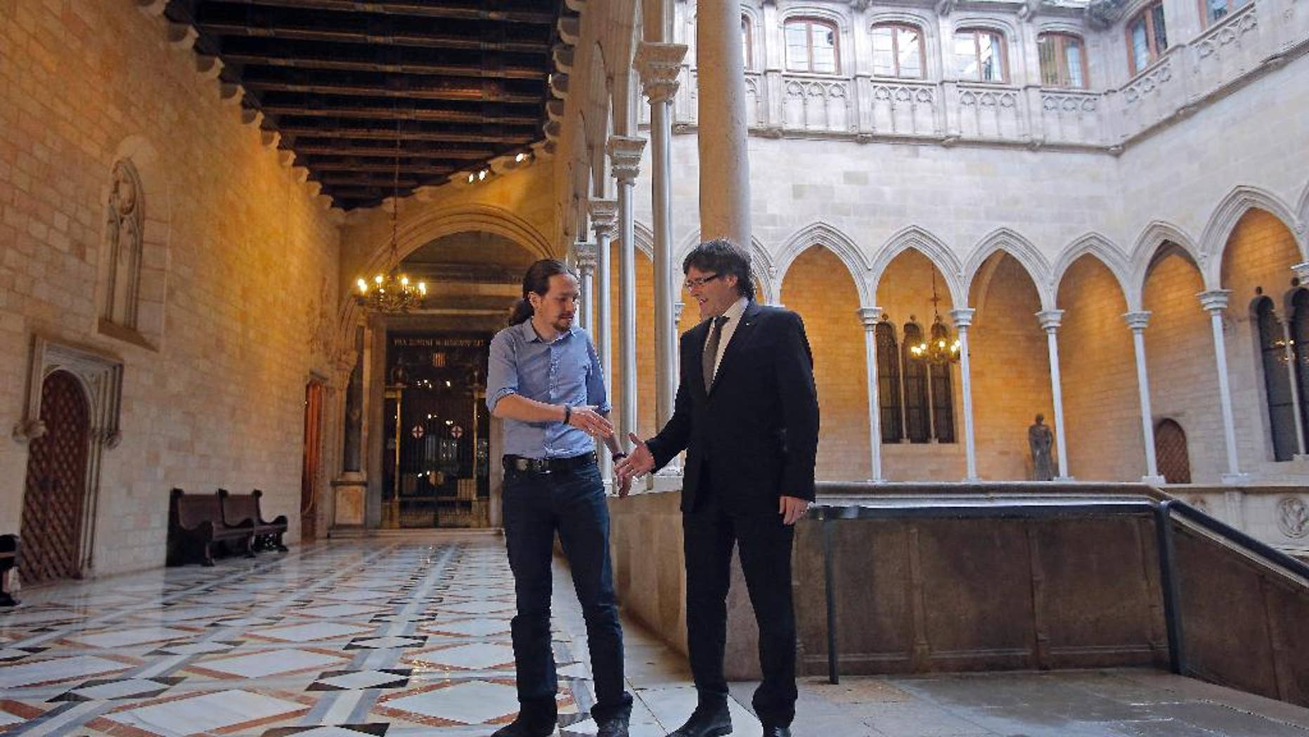 Catalan regional President Carles Puigdemont, right, shakes hands with Podemos Party leader Pablo Iglesias at the Generalitat Palace in Barcelona, Spain, Friday, April 8, 2016. The leader of Spain's far left Podemos party has announced party members will vote next week on whether to support or oppose a deal to form a government and end nearly four months of political stalemate. Pablo Iglesias made the announcement Friday, a day after he met with negotiators for the Socialists and the centrist Ciudadanos party. They have a deal to form a government but lack parliamentary support and could get it from Podemos. (AP Photo/Manu Fernandez)