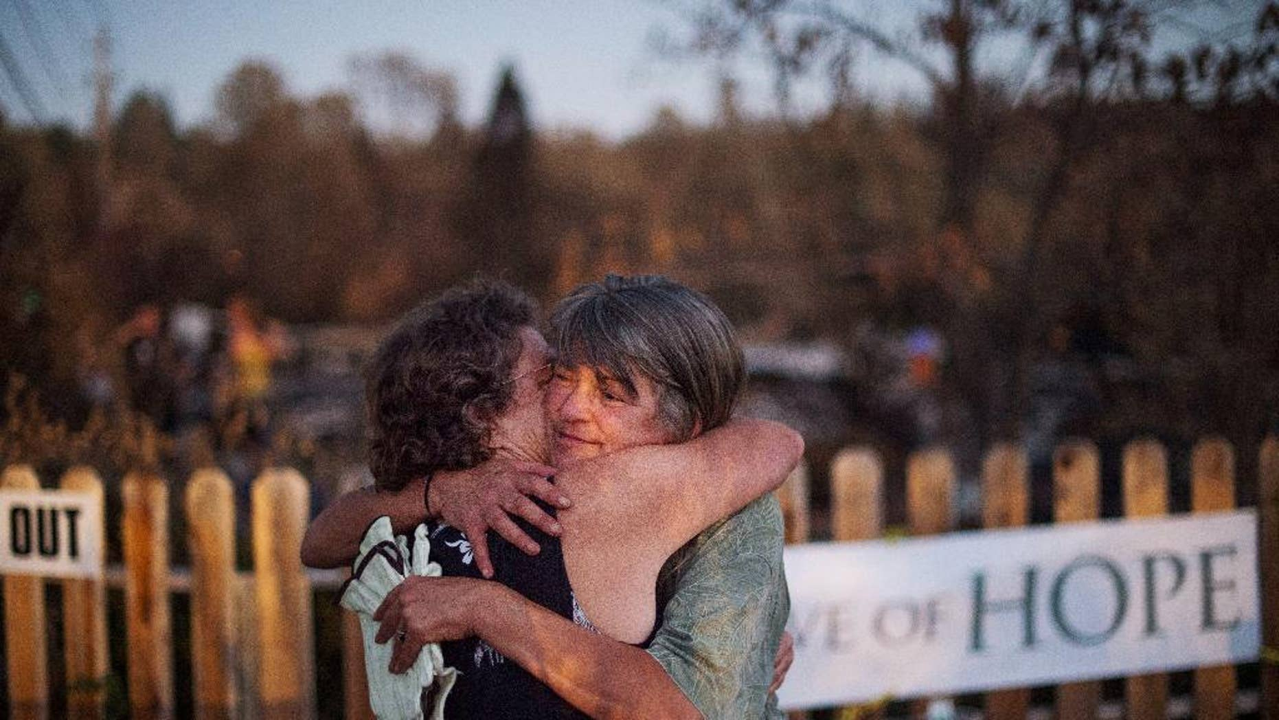 Sharon Dawson, right, who lost her home in a wildfire, embraces a friend while visiting her Middletown, Calif., property on Monday, Sept. 21, 2015. Gov. Jerry Brown requested a presidential disaster declaration on Monday, noting that more than 1,000 homes had been confirmed destroyed, with the number likely to go higher as assessment continues. (AP Photo/Noah Berger)