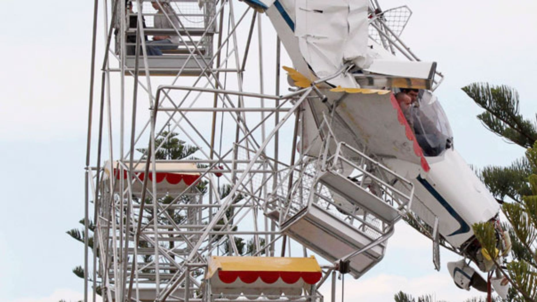 Oct. 1: Two men and their ultra-light plane hang from a Ferris wheel while two children sit in a carriage near the top of the ride at a country festival at Old Bar, Australia.
