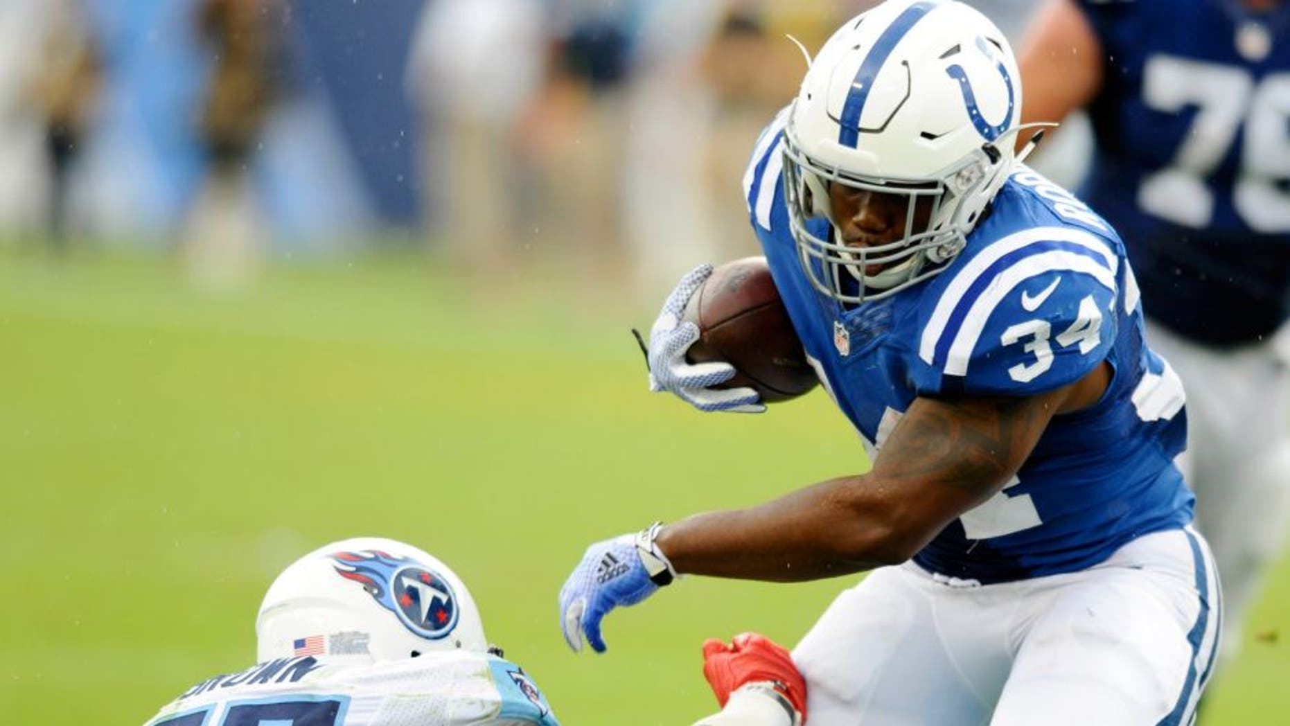 Sep 27, 2015; Nashville, TN, USA; Indianapolis Colts running back Josh Robinson (34) fights off a tackle during the second half against the Tennessee Titans at Nissan Stadium. The Colts won 35-33. Mandatory Credit: Christopher Hanewinckel-USA TODAY Sports