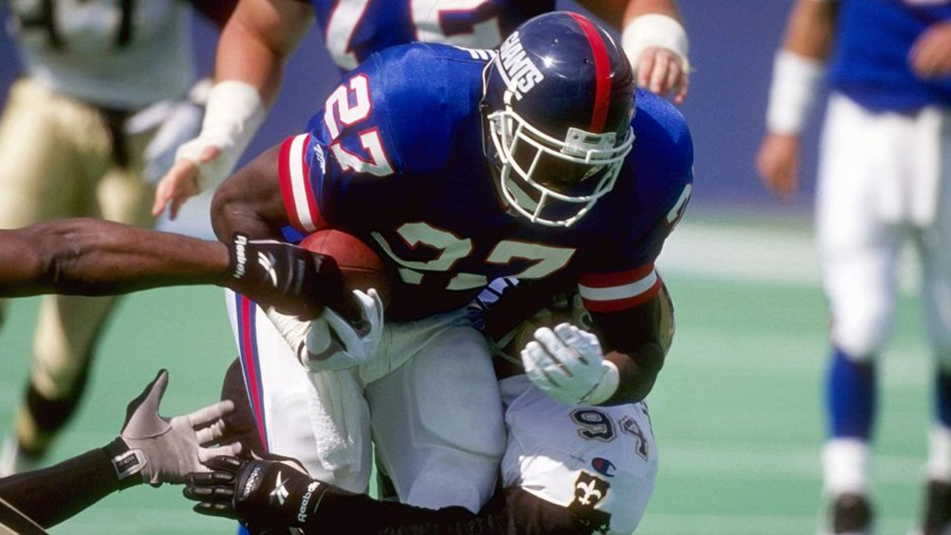 24 Sep 1995: Running back Rodney Hampton #27 of the New York Giants attempts to run through the tackle of defensive lineman Joe Johnson #94 of the New Orleans Saints during a game held at the Meadowlands in East Rutherford, New Jersey. The Giants won th