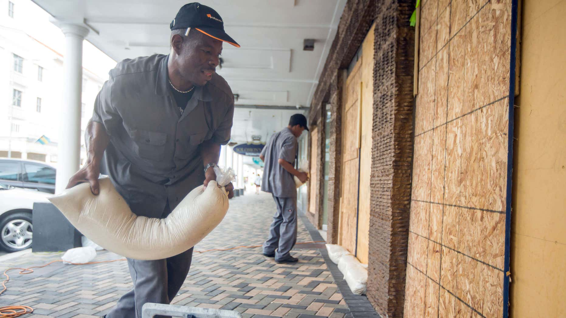 Oct. 1, 2015: Perry Williams, 47, left, and Alaric Nixon, 28, place sandbags on the storefront of Diamond's International store, in preparation for the arrival of hurricane Joaquin in Nassau, Bahamas.