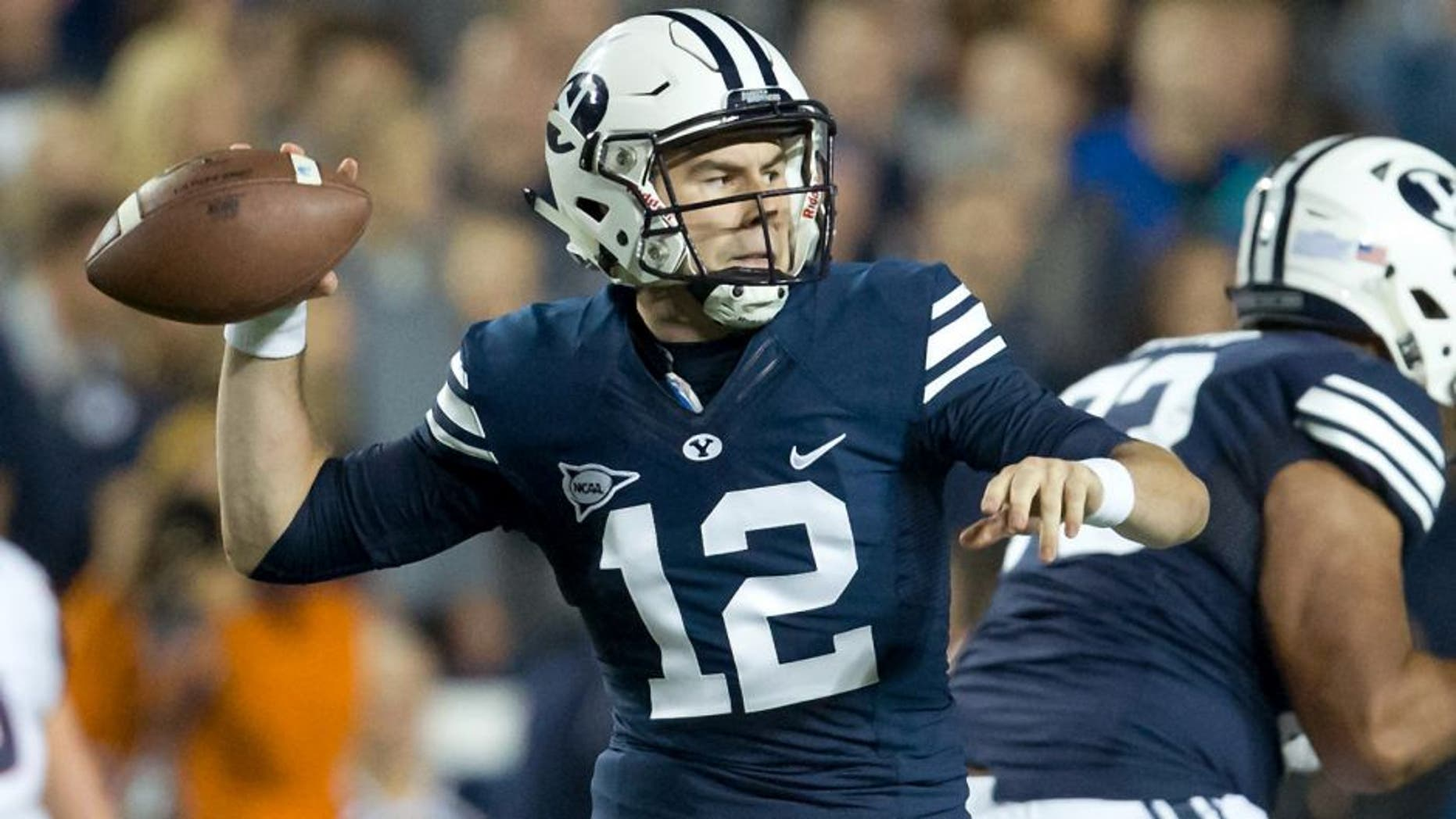 Oct 2, 2015; Provo, UT, USA; Brigham Young Cougars quarterback Tanner Mangum (12) passes the ball during the first quarter against the Connecticut Huskies at Lavell Edwards Stadium. Mandatory Credit: Russ Isabella-USA TODAY Sports