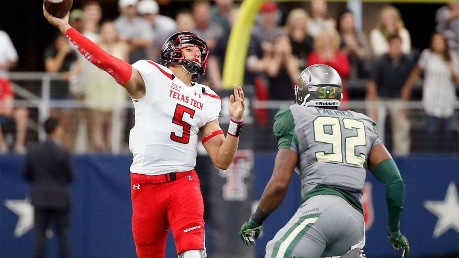 Texas Tech quarterback Patrick Mahomes (5) throws a long touchdown pass to wide receiver Zach Austin under pressure from Baylor defensive end Jamal Palmer (92) in the first half of an NCAA college football game Saturday, Oct. 3, 2015, in Arlington, Texas. (AP Photo/Tony Gutierrez)