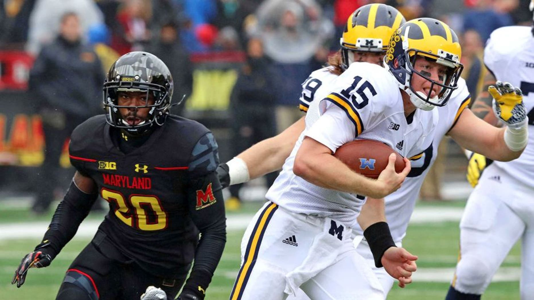 Oct 3, 2015; College Park, MD, USA; Michigan Wolverines quarterback Jake Rudock (15) runs for a gain past Maryland Terrapins defensive back Anthony Nixon (20) at Byrd Stadium. Mandatory Credit: Mitch Stringer-USA TODAY Sports