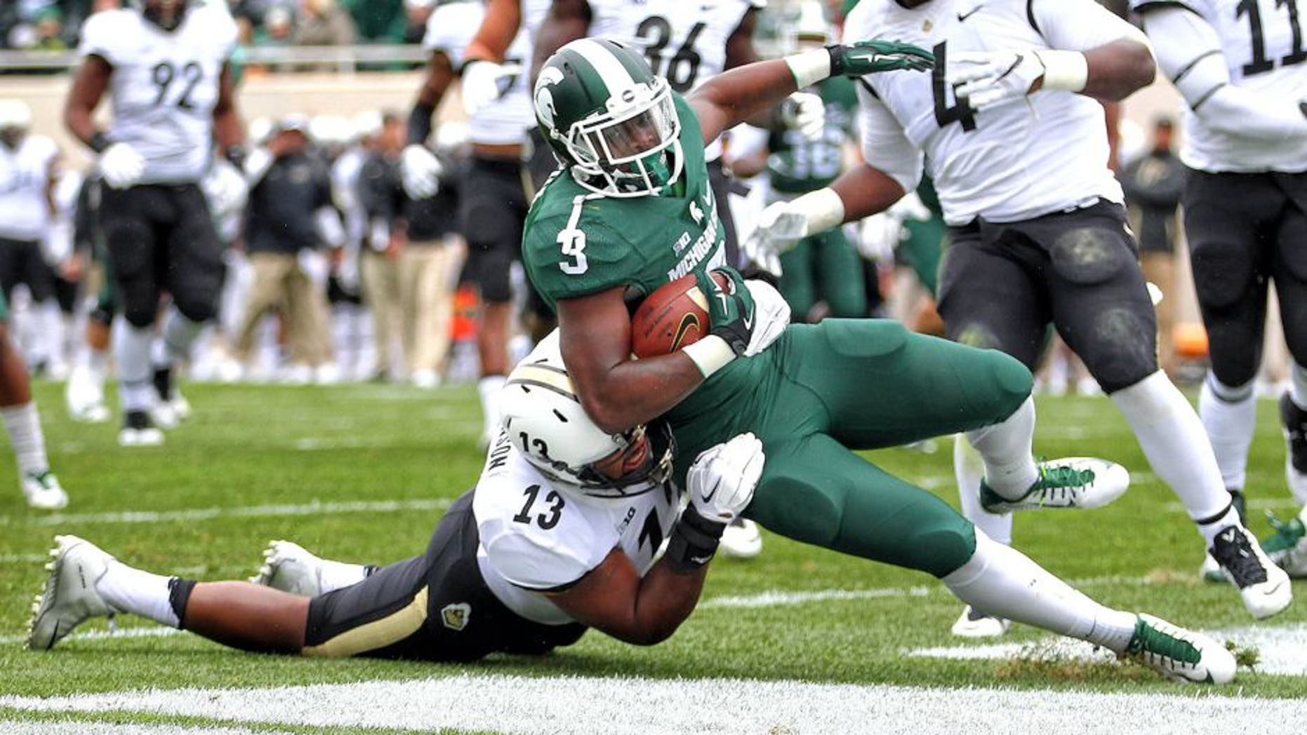 Oct 3, 2015; East Lansing, MI, USA; Michigan State Spartans running back LJ Scott (3) scores a touchdown against Purdue Boilermakers defensive end Gelen Robinson (13) during the 1st quarter of a game at Spartan Stadium. Mandatory Credit: Mike Carter-USA TODAY Sports
