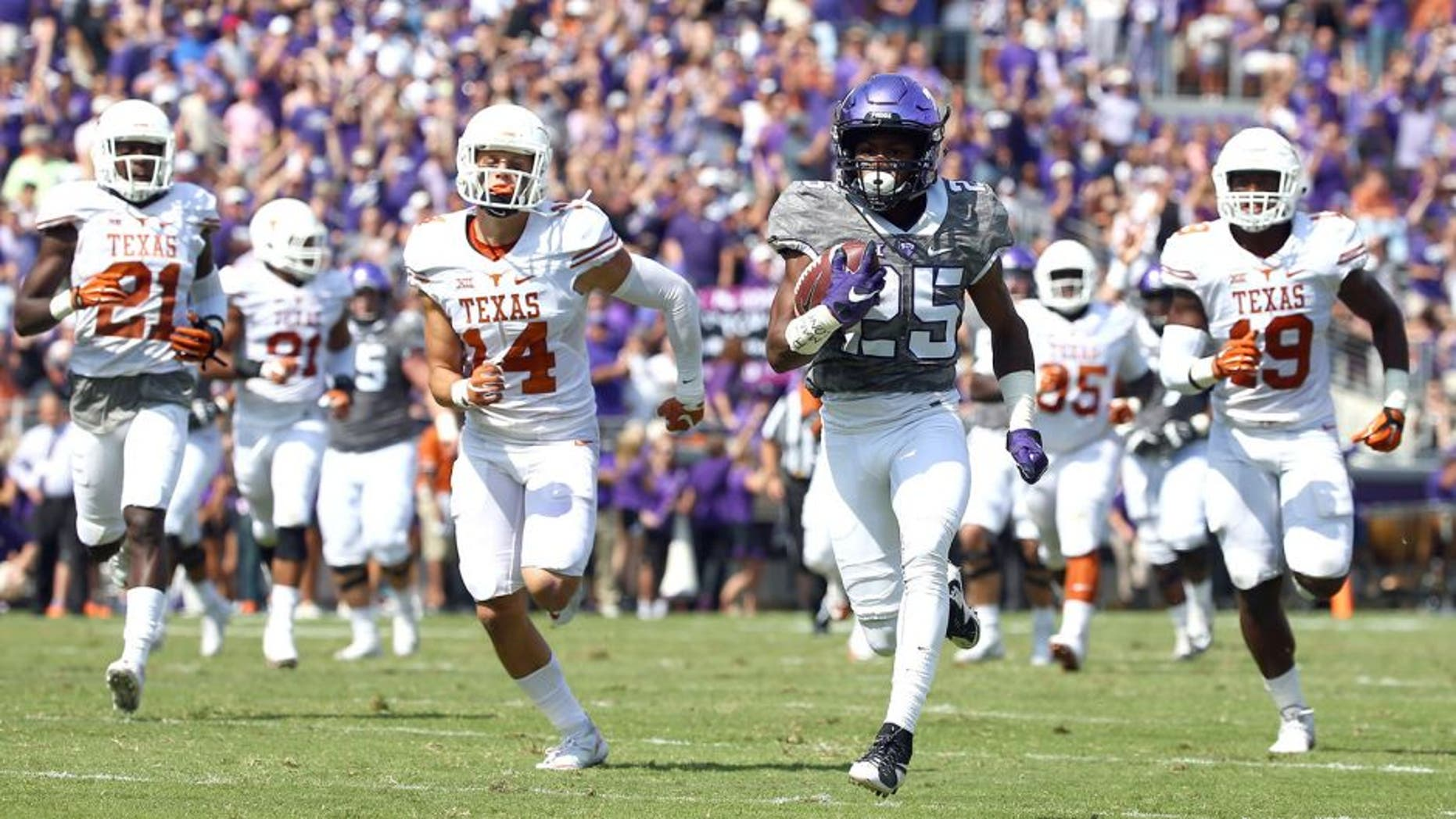 FORT WORTH, TX - OCTOBER 03: KaVontae Turpin #25 of the TCU Horned Frogs carries the ball for a touchdown against Duke Thomas #21 of the Texas Longhorns, Dylan Haines #14 of the Texas Longhorns, Peter Jinkens #19 of the Texas Longhorns in the second quarter at Amon G. Carter Stadium on October 3, 2015 in Fort Worth, Texas. (Photo by Tom Pennington/Getty Images)