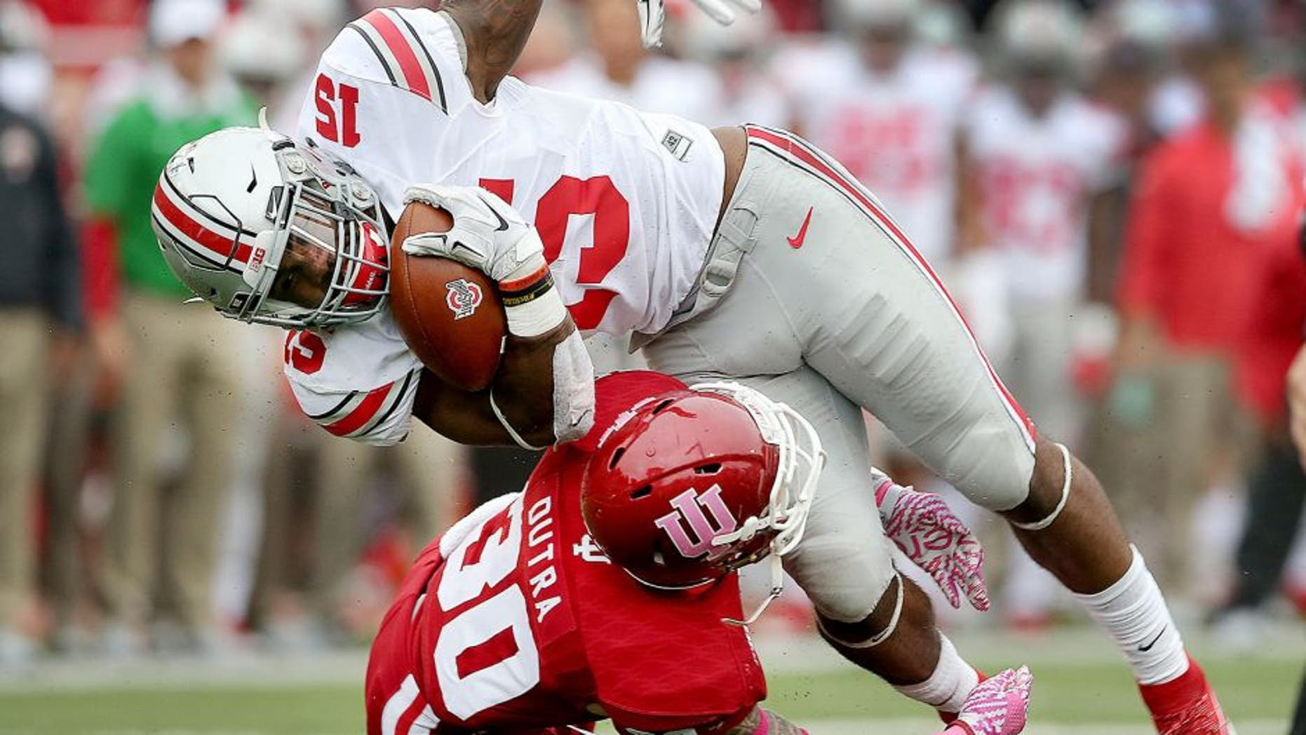 Oct 3, 2015; Bloomington, IN, USA; Ohio State Buckeyes running back Ezekiel Elliott (15) is stopped by Indiana Hoosiers defensive back Chase Dutra (30) in the first half of their game at Memorial Stadium. Mandatory Credit: Matt Kryger-USA TODAY Sports