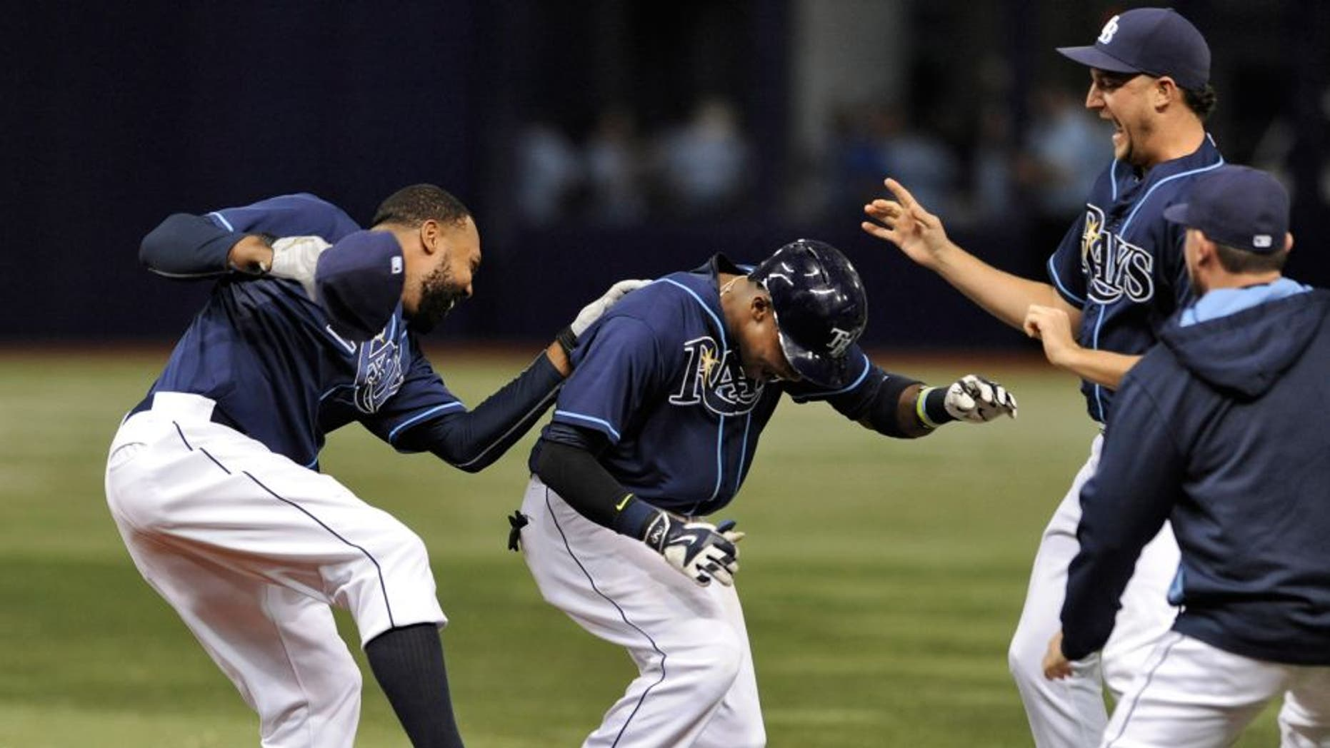 Tampa Bay Rays' Joey Butler, left, and Brad Boxberger, second from right, celebrate with Tim Beckham, center, after Beckham's two-run walk-off single to beat the Toronto Blue Jays 4-3 during the ninth inning of a baseball game Saturday, Oct. 3, 2015, in St. Petersburg, Fla. (AP Photo/Steve Nesius)