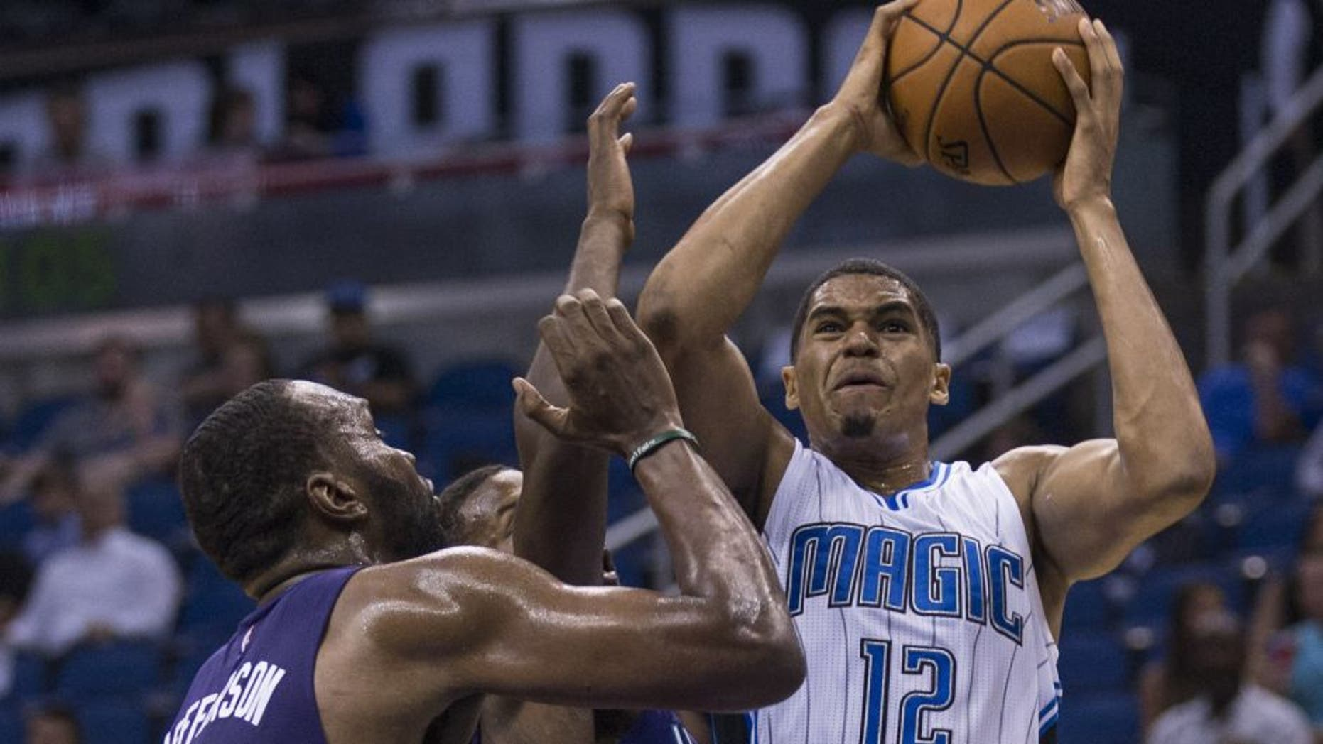 Orlando Magic forward Tobias Harris (12) shoots the ball and scores over Charlotte Hornets forward Sam Thompson (12) center and Charlotte Hornets center Al Jefferson (25) right, during the first half of an NBA basketball game in Orlando, Fla., Saturday, Oct. 3, 2015. (AP Photo/Willie J. Allen Jr.)