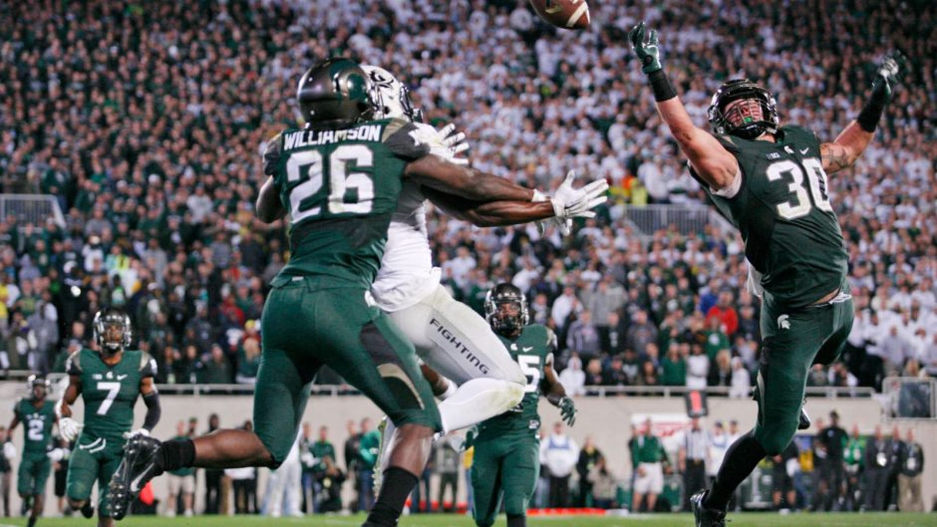 Sep 12, 2015; East Lansing, MI, USA; Michigan State Spartans linebacker Riley Bullough (30) and safety Rj Williamson (26) defend Oregon Ducks wide receiver Byron Marshall (9) during the fourth quarter at Spartan Stadium. Spartans beat the Ducks 31-28. Mandatory Credit: Raj Mehta-USA TODAY Sports