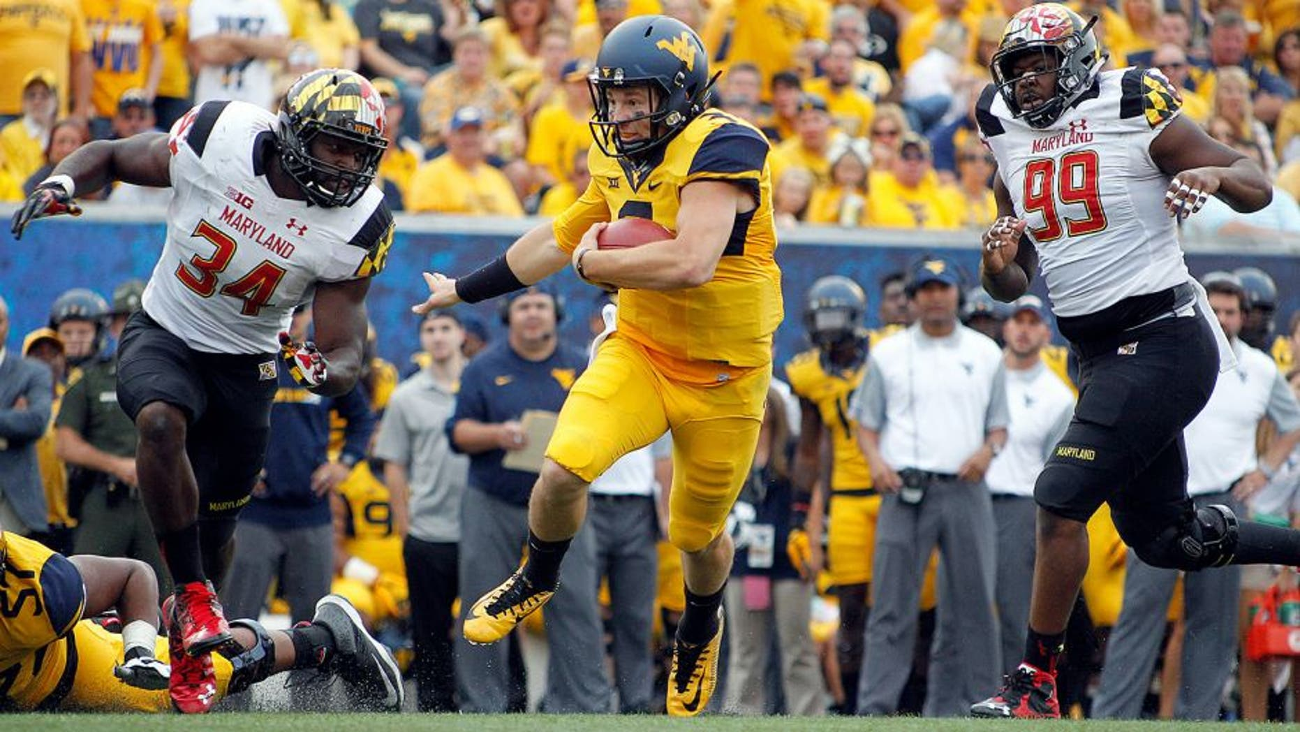 MORGANTOWN, WV - SEPTEMBER 26: Skyler Howard #3 of the West Virginia Mountaineers rushes against Quinton Jefferson #99 and Jefferson Ashiru #34 of the Maryland Terrapins during the game on September 26, 2015 at Mountaineer Field in Morgantown, West Virginia. (Photo by Justin K. Aller/Getty Images)