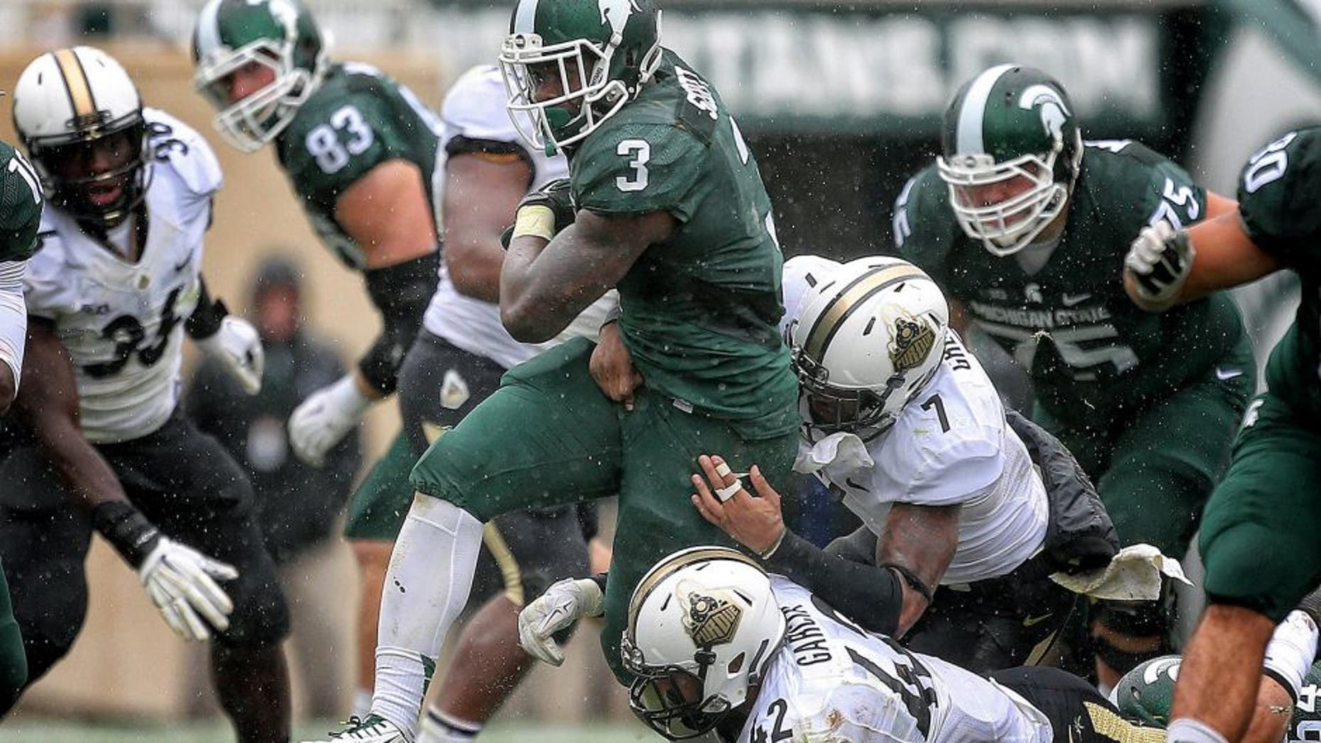 Oct 3, 2015; East Lansing, MI, USA; Michigan State Spartans running back LJ Scott (3) is tackled by Purdue Boilermakers linebacker Andy James Garcia (42) and Purdue Boilermakers safety Robert Gregory (7) during the 2nd half of a game at Spartan Stadium. MSU won 24-21. Mandatory Credit: Mike Carter-USA TODAY Sports